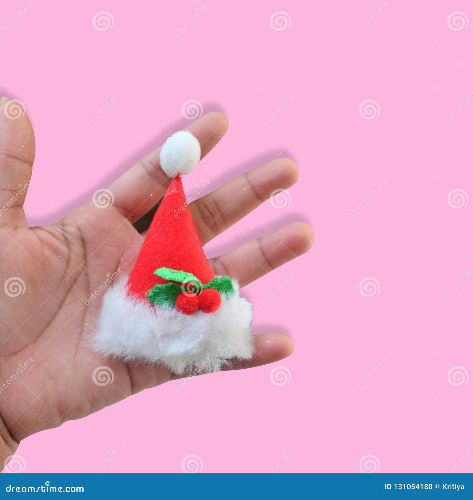 Handen rymmer den julsantas hatten på pastellfärgad rosa bakgrund minim