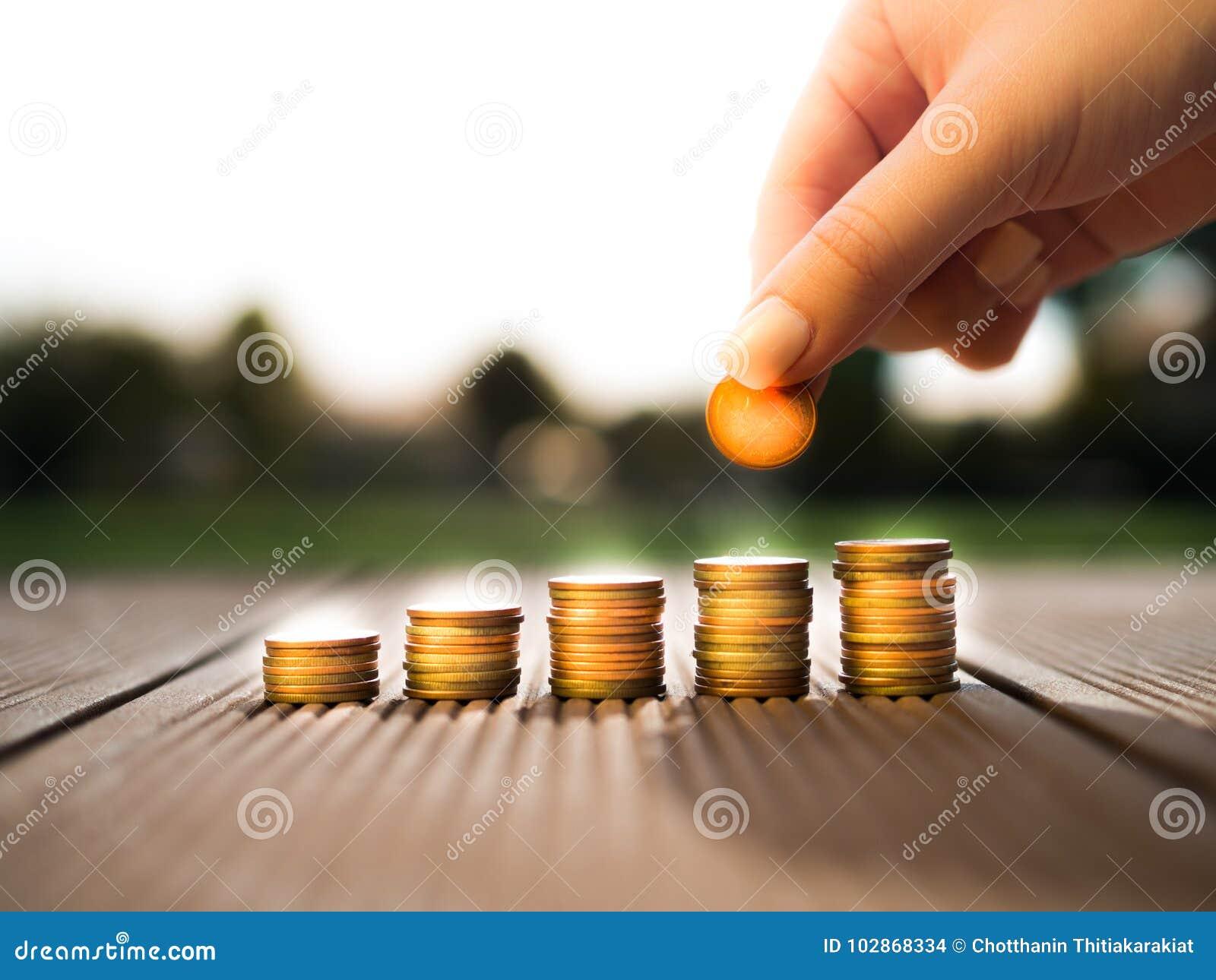 Handen som sätter pengarmynt, staplar att växa som sparar pengar för avsiktbegrepp