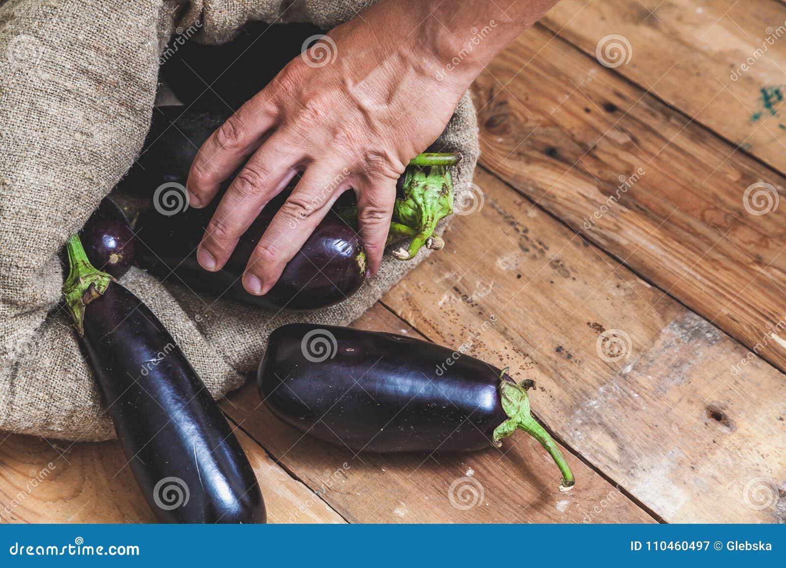 Handen tar aubergine från påse på träbräden