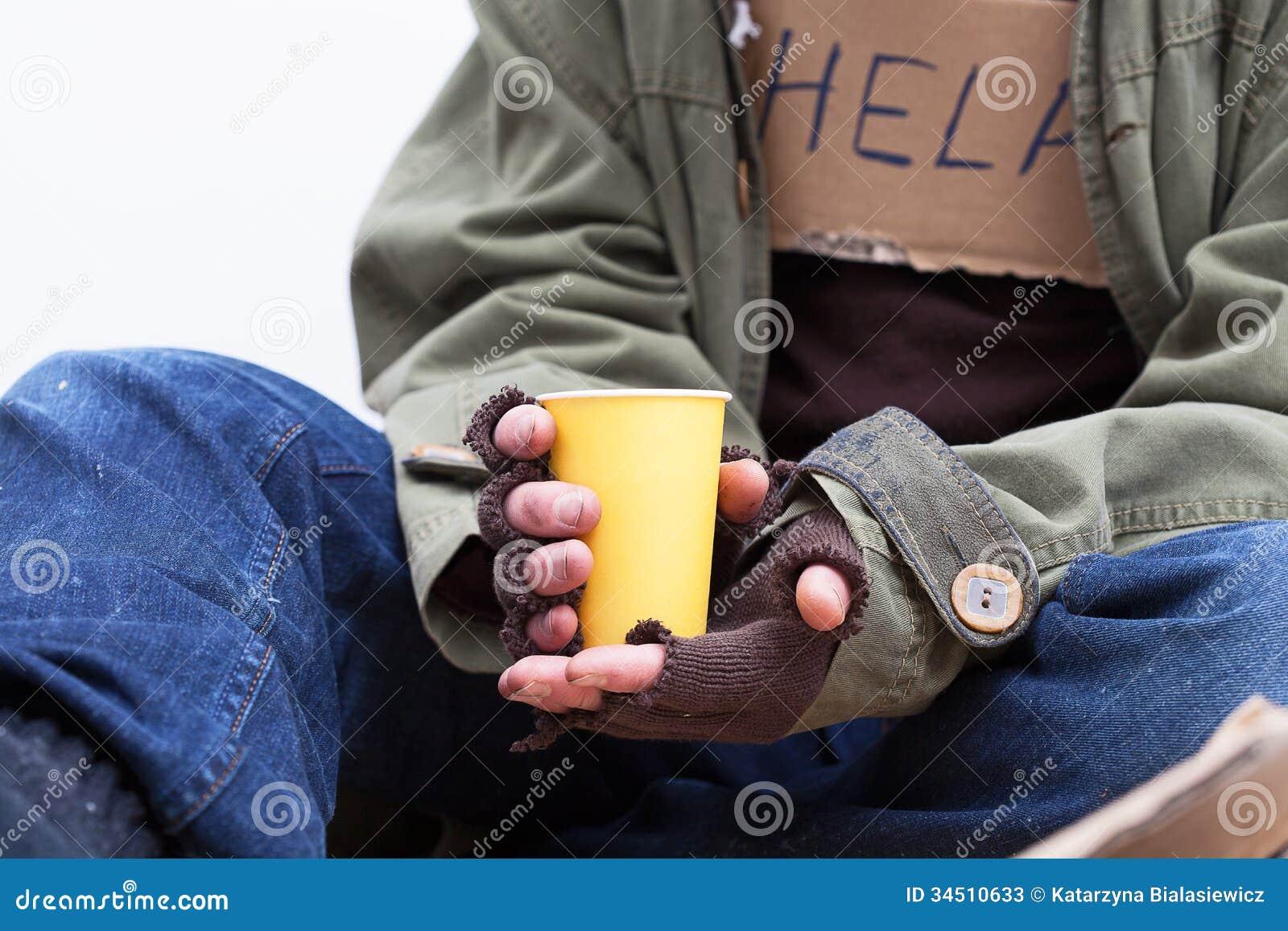 Handen van daklozen met een document kop