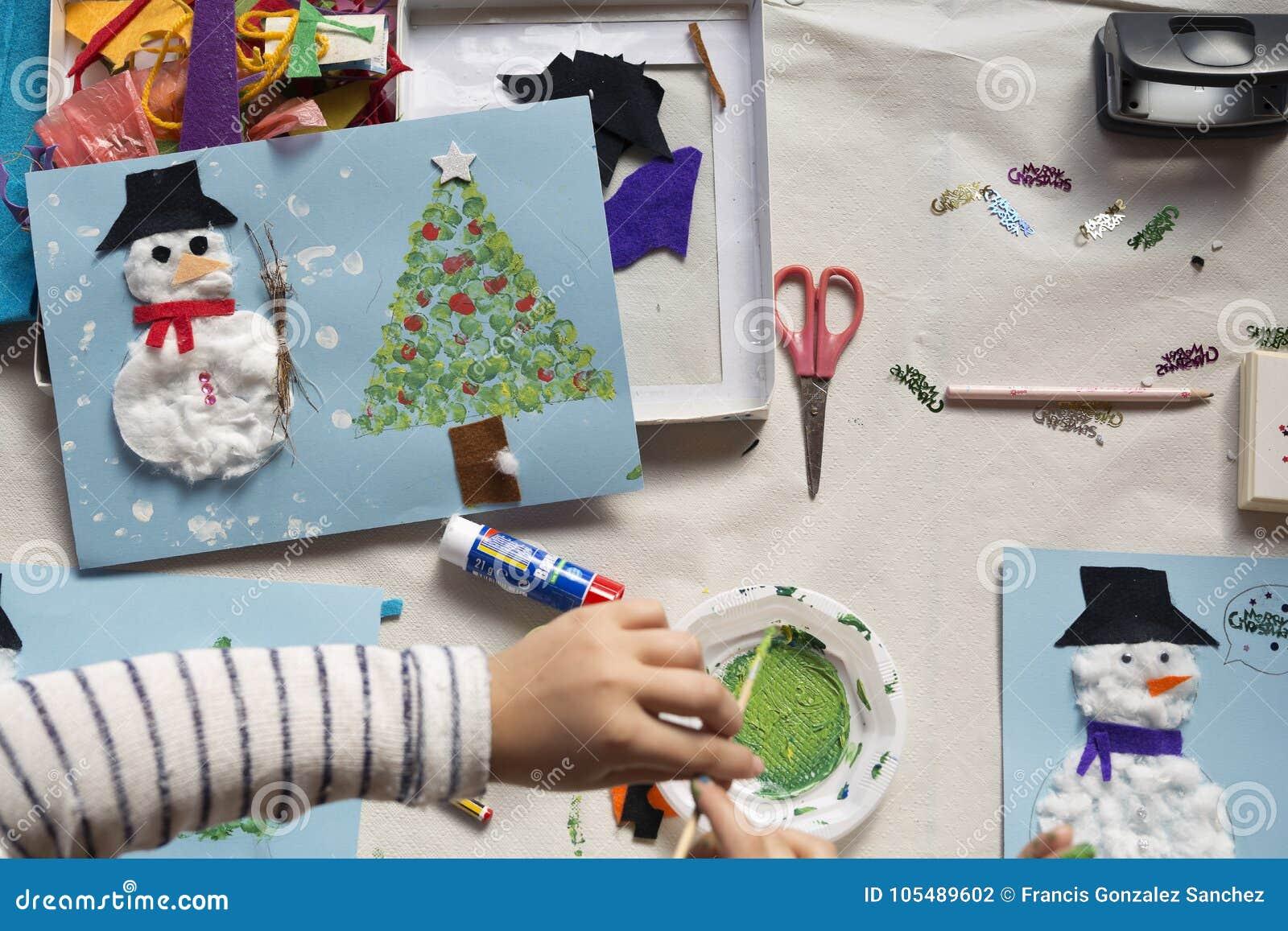 Handen van een 10 éénjarigenmeisje die een Kerstmisambacht doen