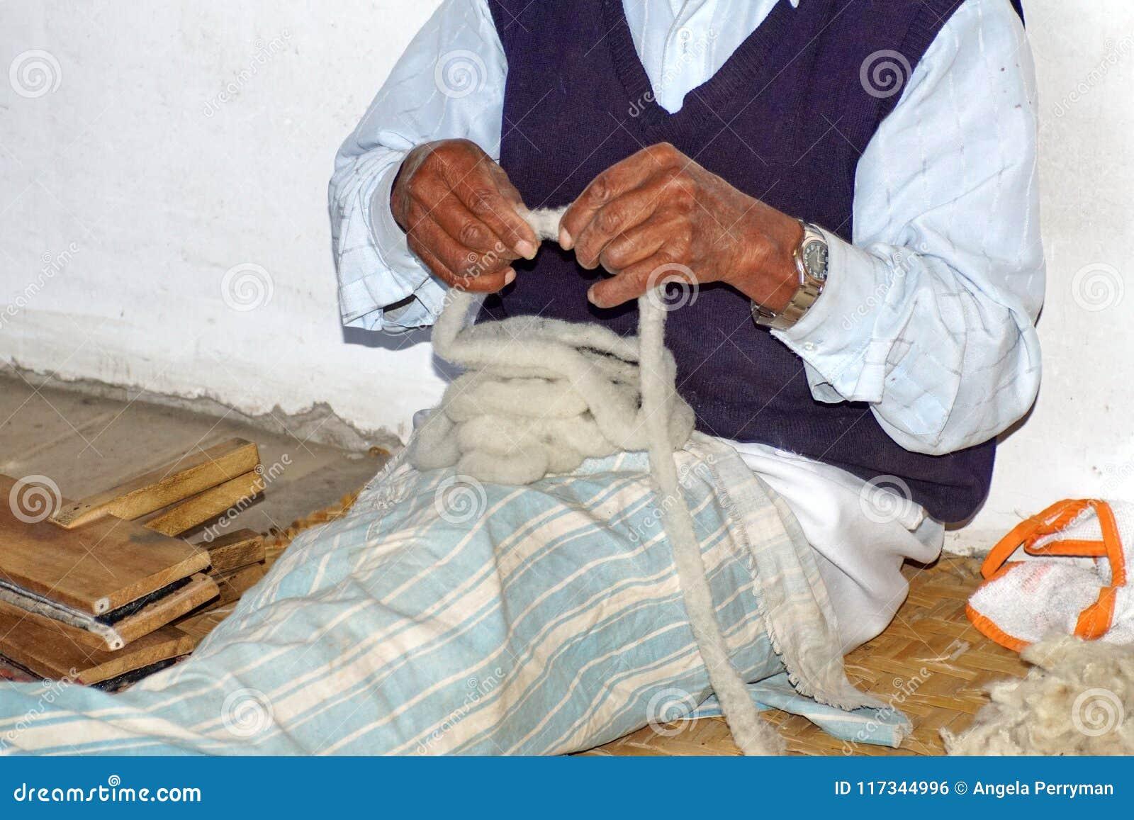 Handen van een bejaarde wever in Ecuador