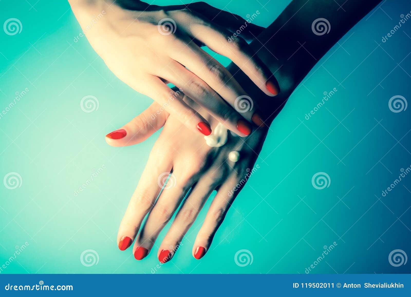 Handen van een jong meisje met rode spijkers en dalingen van room Close-up op een blauwe achtergrond Wijnoogst, grunge retro stij