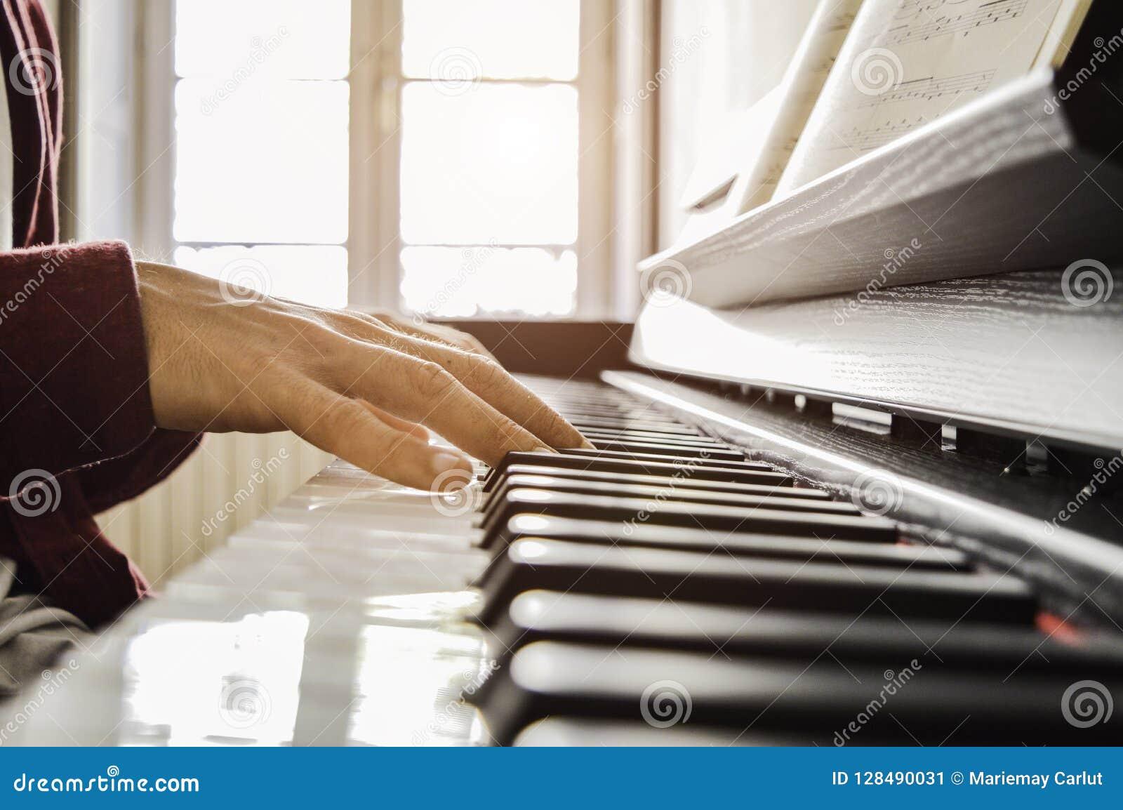 Handen van een jonge mens het spelen piano die een score lezen bij het zonlicht
