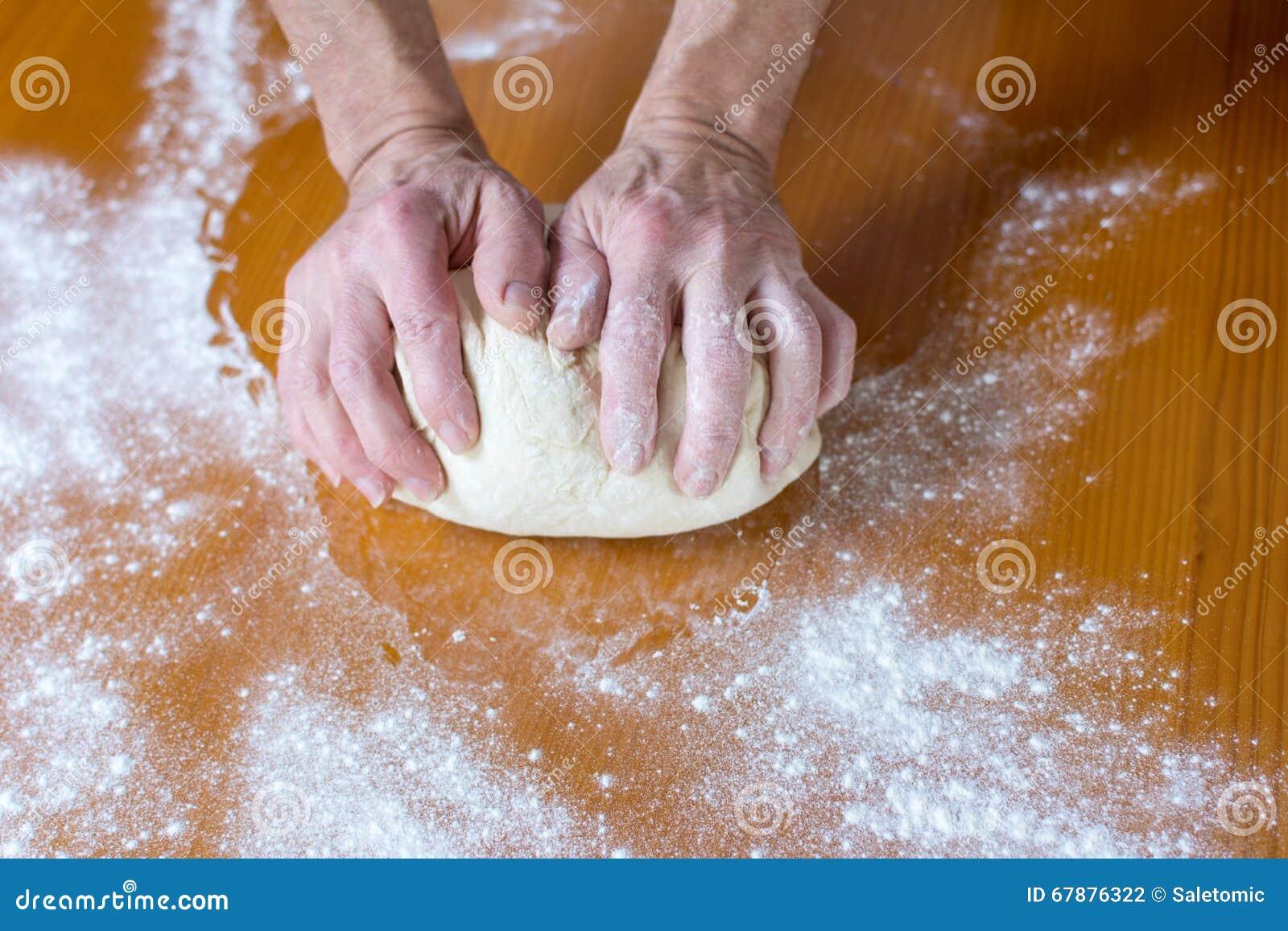 Handen van een mannelijke bakker die brood maken