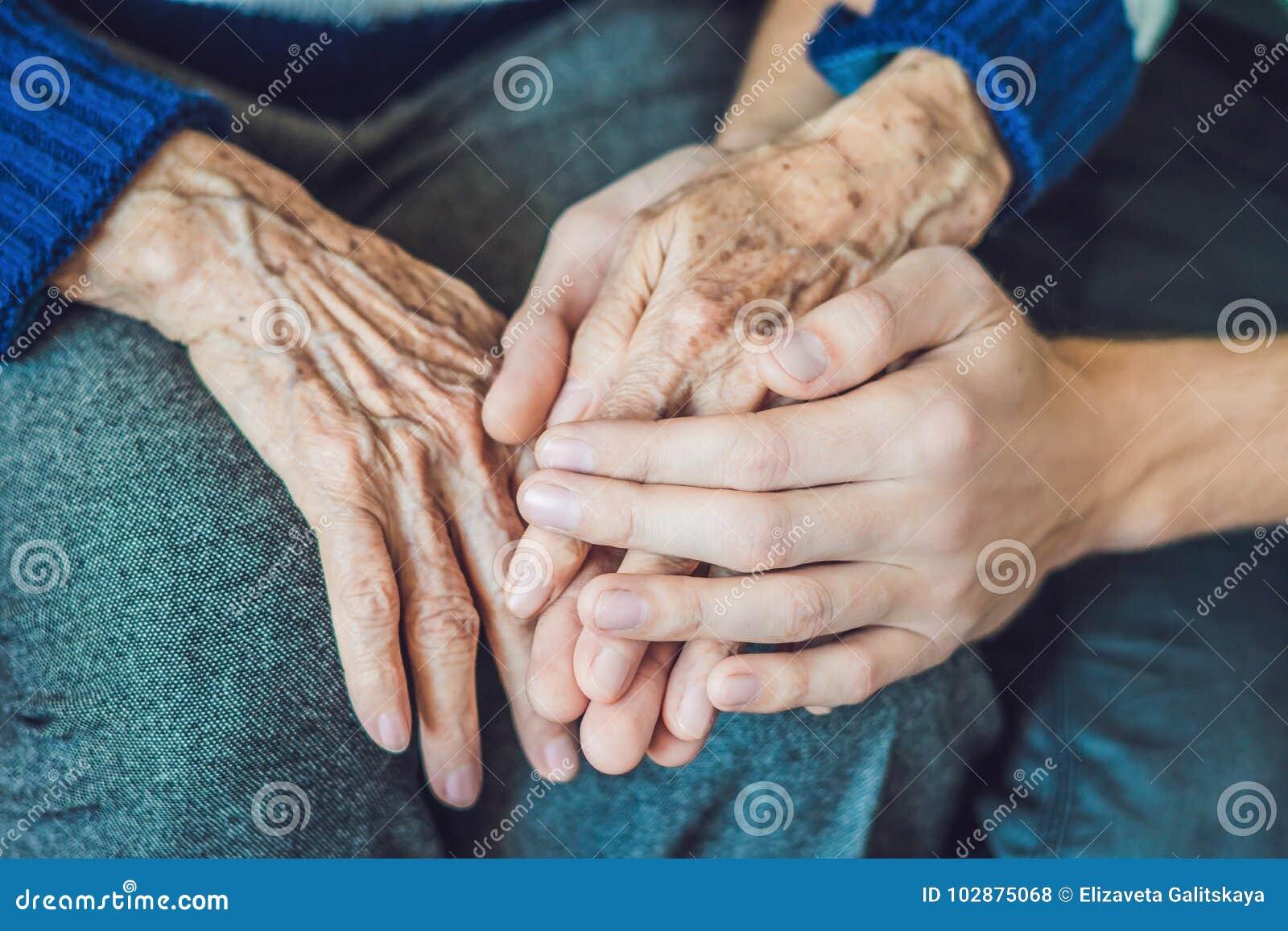 Handen van een oude vrouw en een jonge man Het geven voor de bejaarden C
