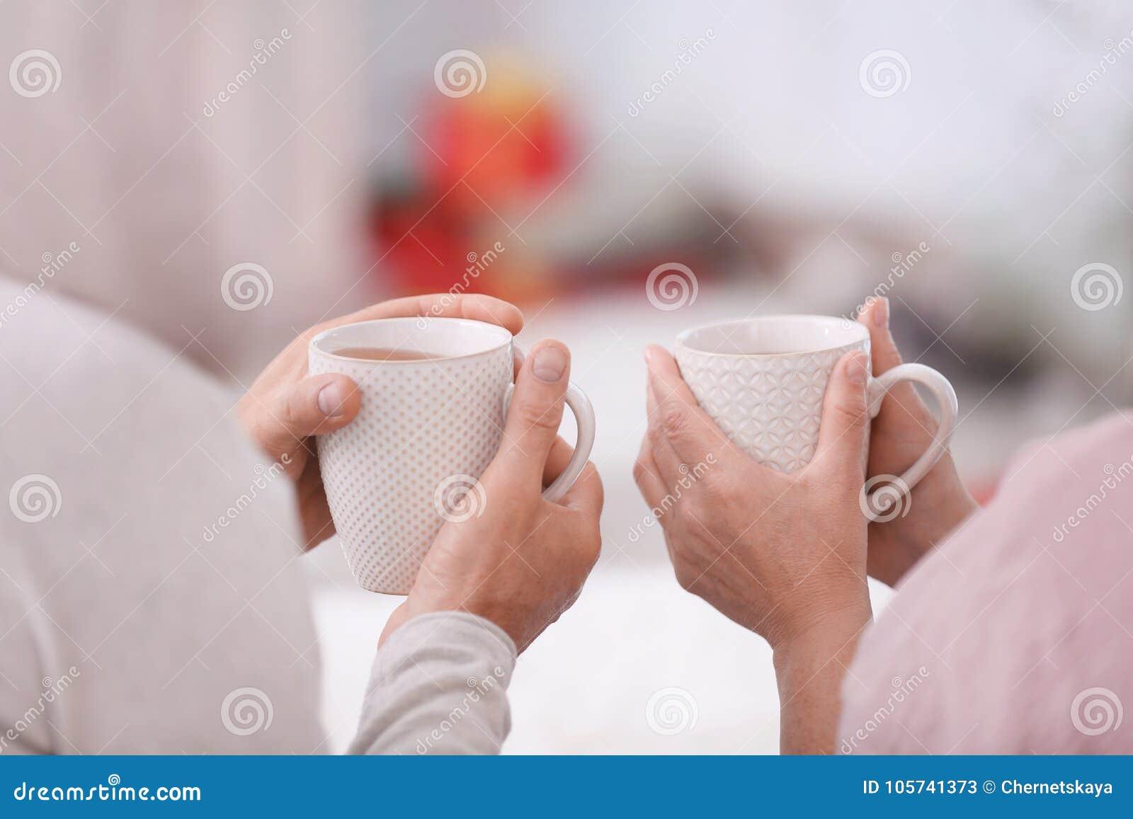 Handen van gelukkig hoger paar die hete thee thuis drinken