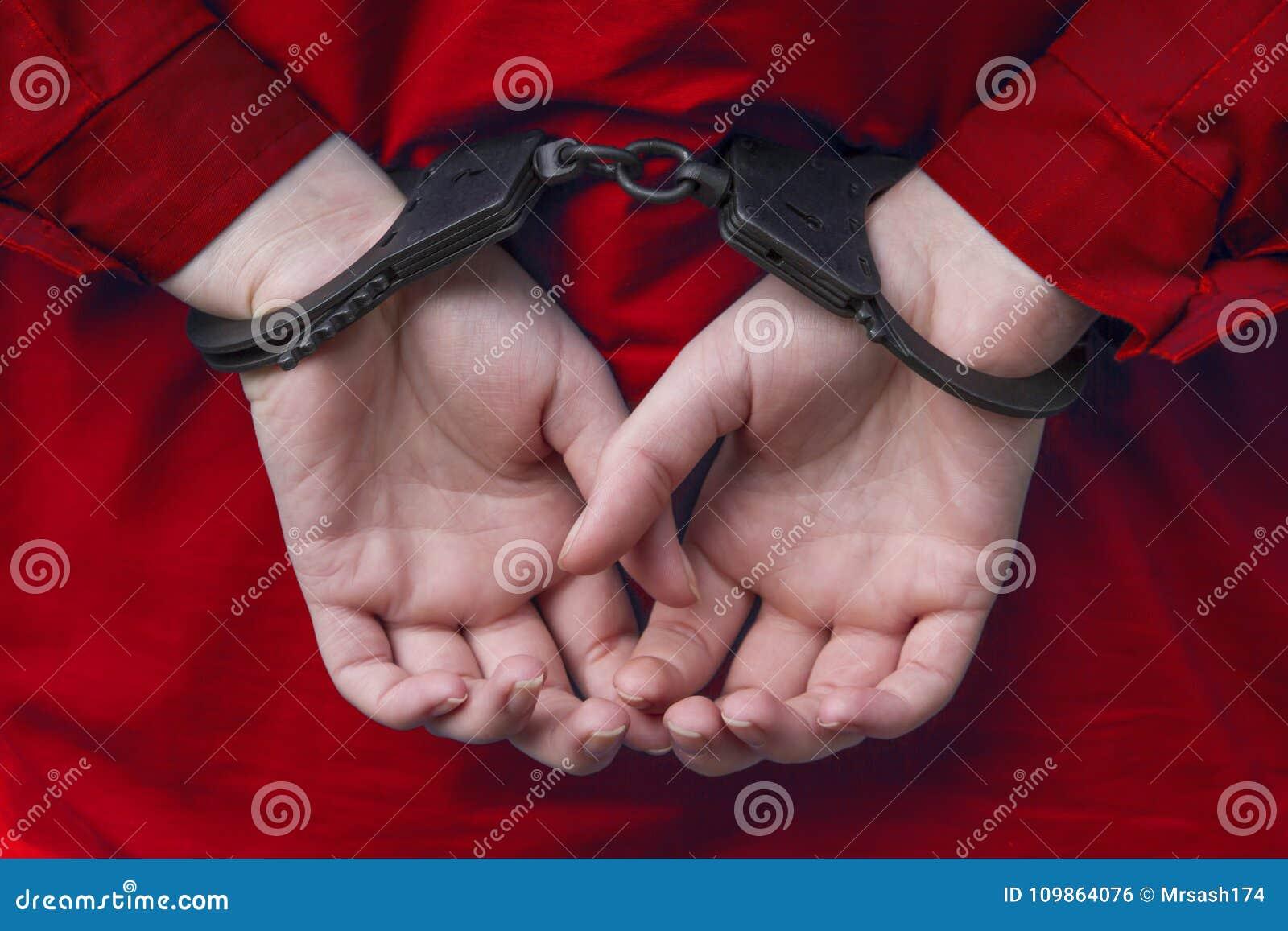 Handen van het meisje in handcuffs Rode kleren