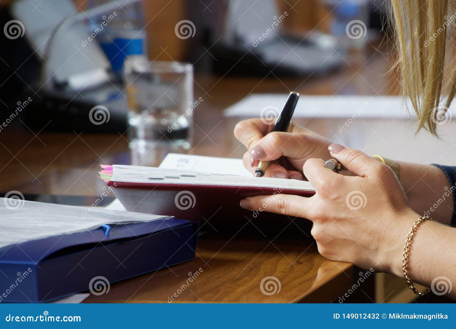 Handen van jonge vrouw het schrijven nota s in een agenda