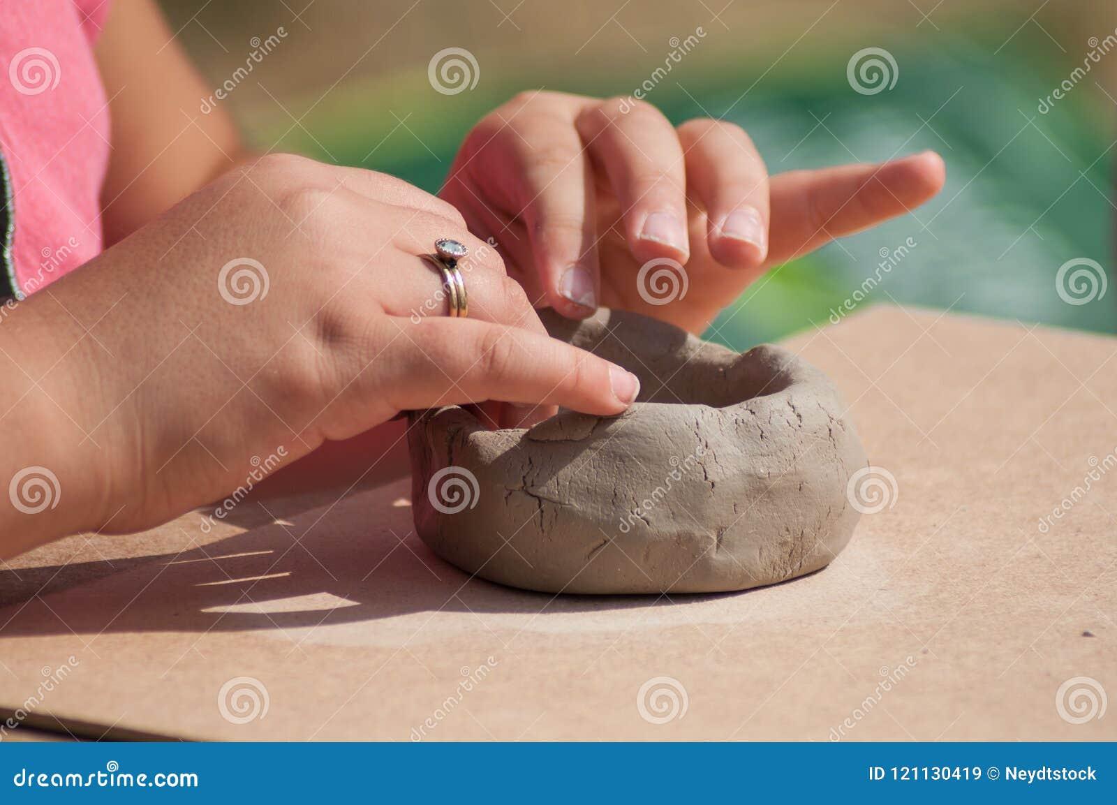 Handen van kind die de kom van het kleiaardewerk in openlucht maken