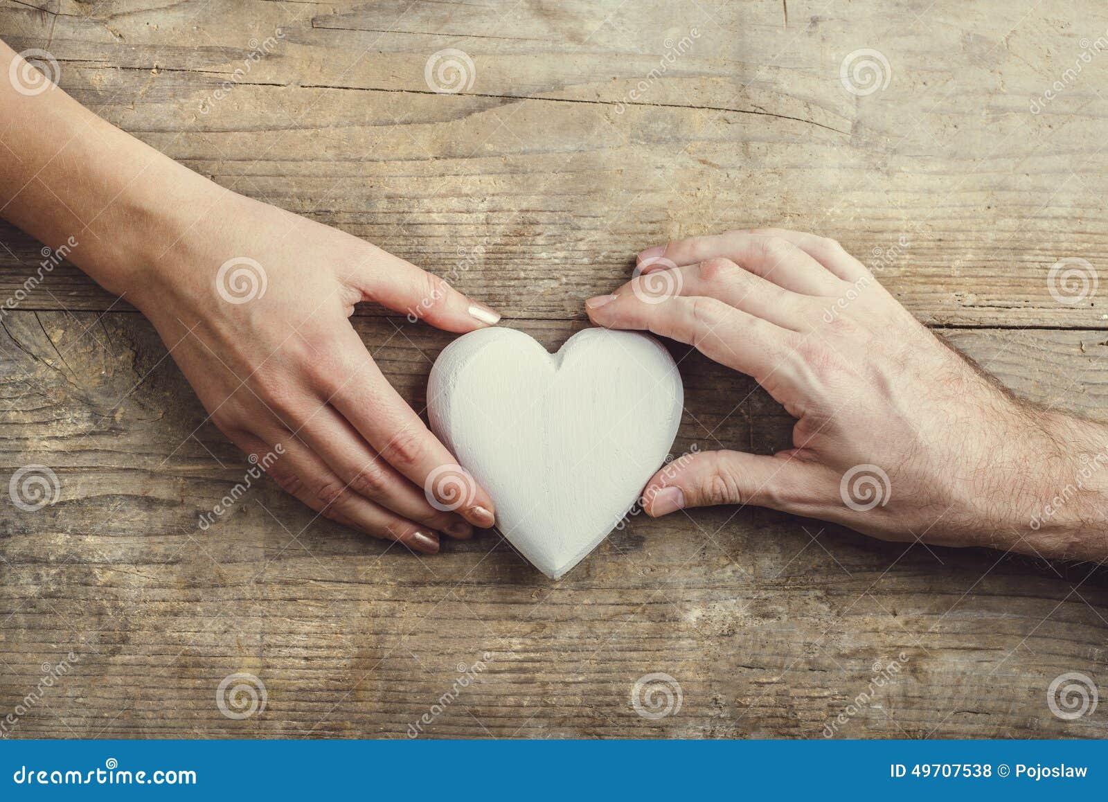 Handen van mens en vrouw door een hart wordt de verbonden dat