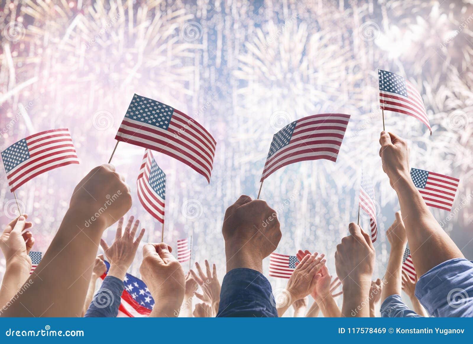 Handen van mensen die de Vlaggen van de V.S. houden