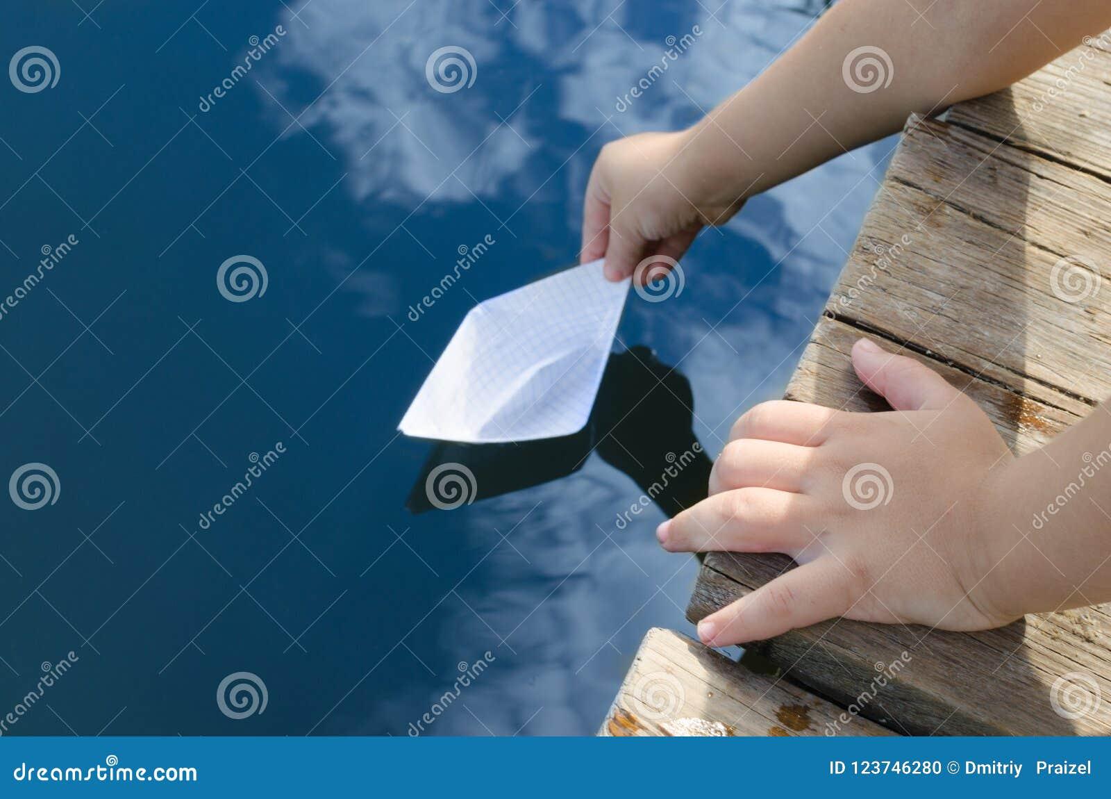 Handen van weinig jongen, versies in de waterdocument boot met houten pijler