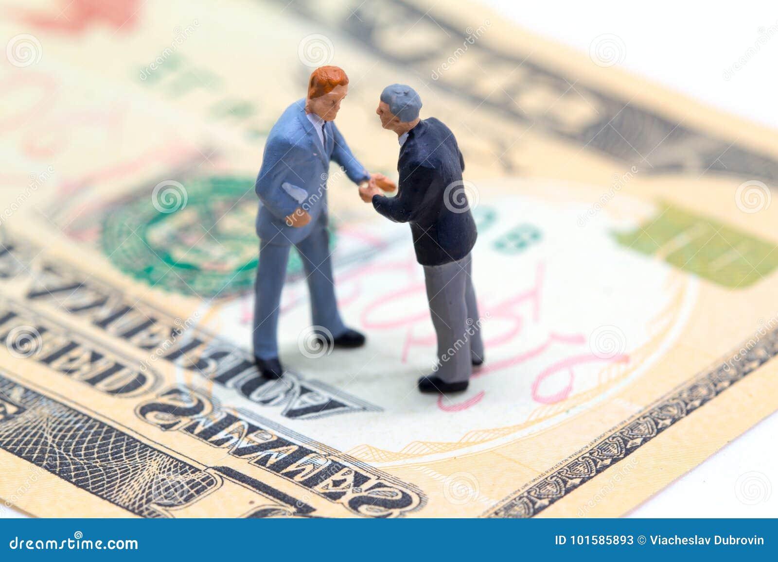 Handenschuddenzakenlieden op de dollarbankbiljet van de V.S. Bedrijf voordelige overeenkomst