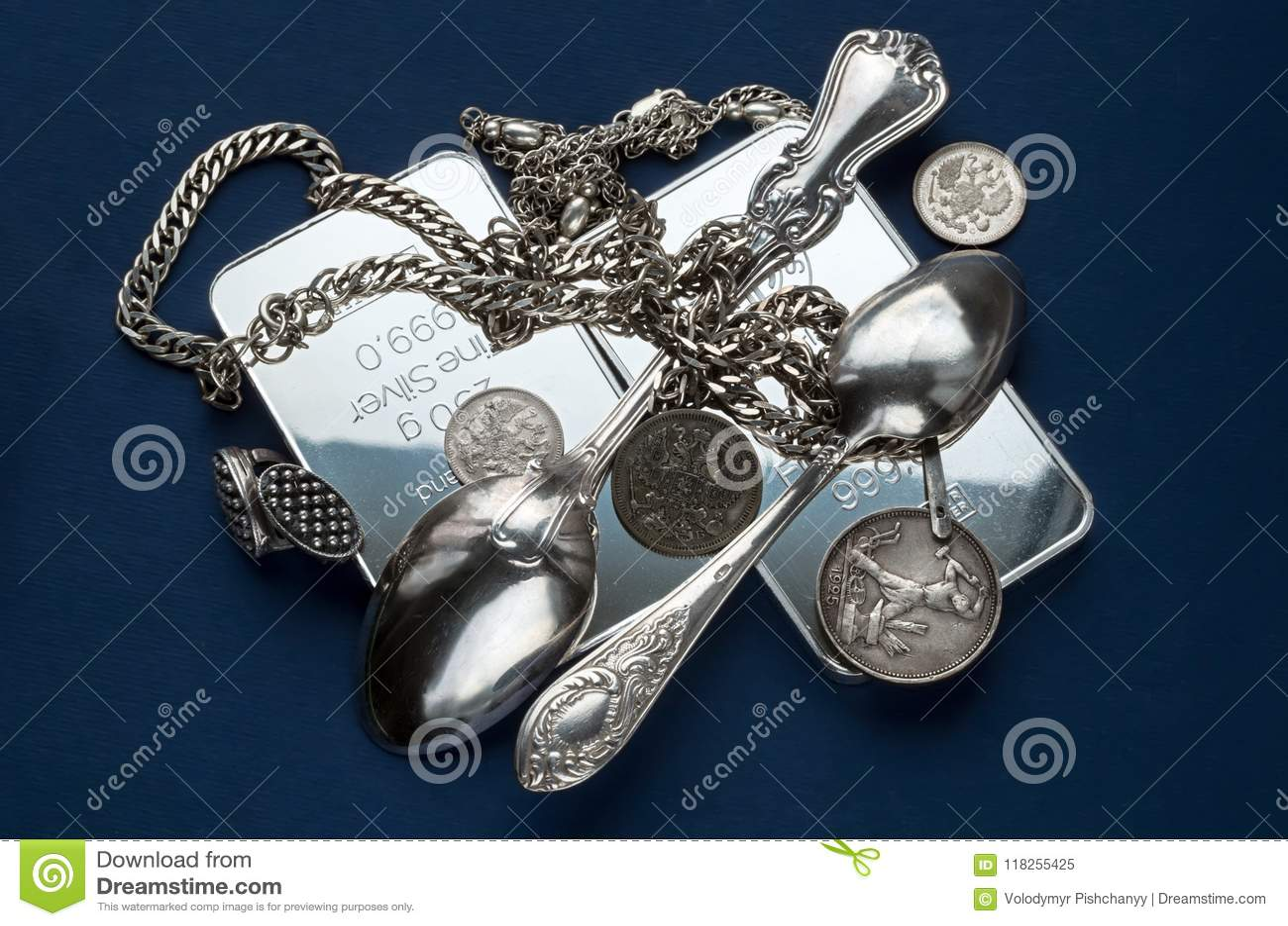 Handfullen silverguldtacka, ett bestick, smycken och gamla silvermynt på ett mörker - blå bakgrund