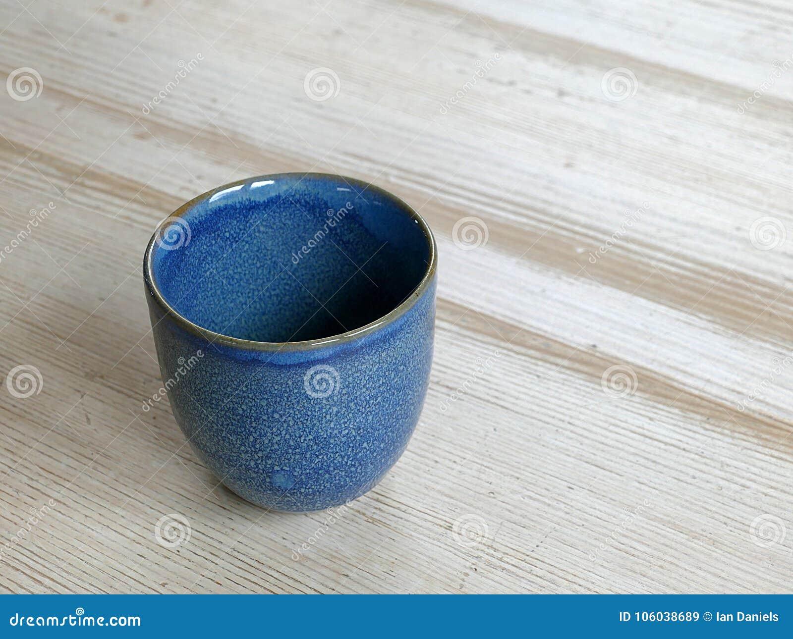 Handgemachte blaue Kaffeetasse auf einem Holztisch