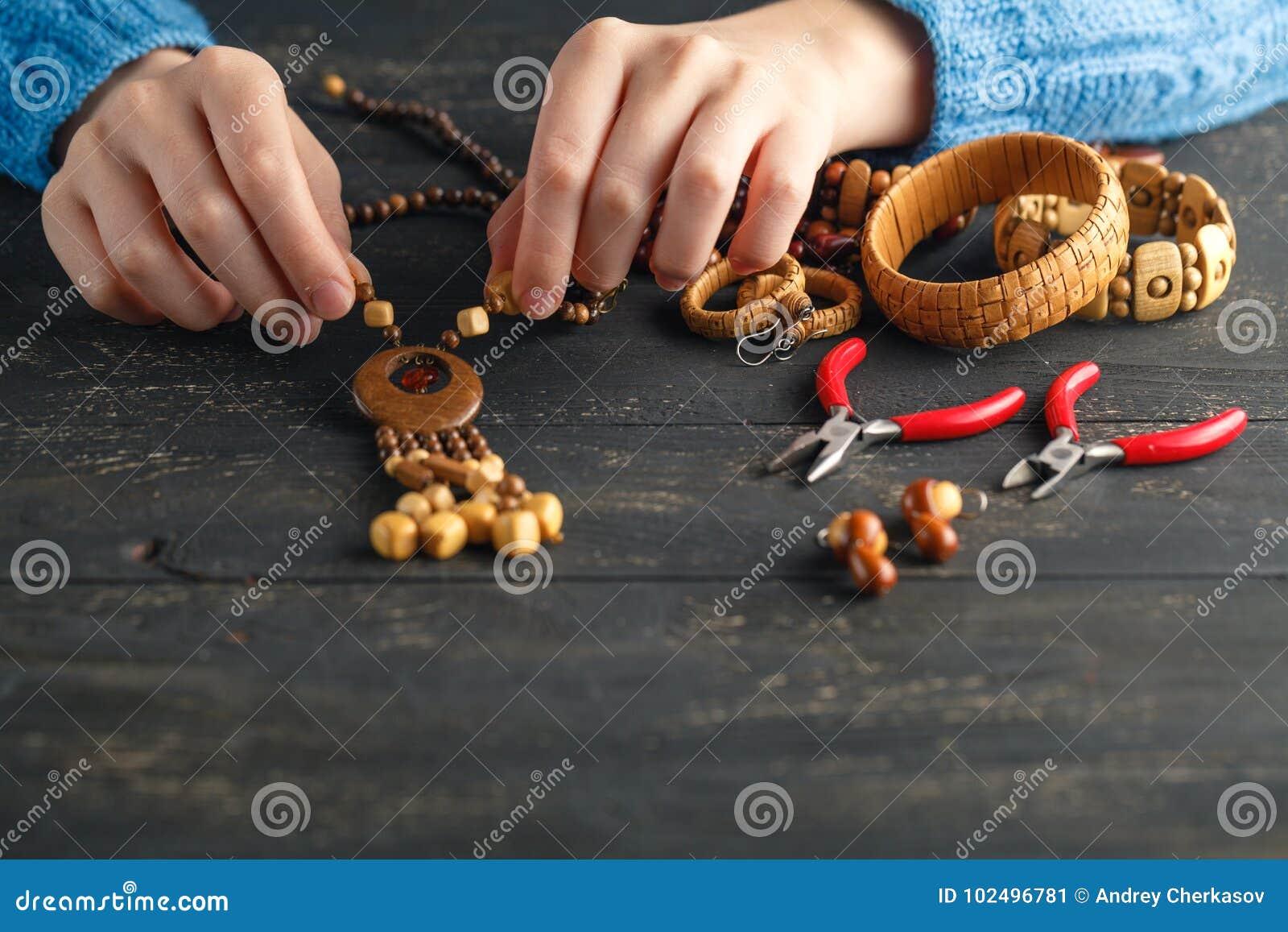 Handgemachte machende Ohrringe, Hauptwerkstatt Frauenhandwerker stellen Quastenschmuck her Kunst, Hobby, Handwerkskonzept