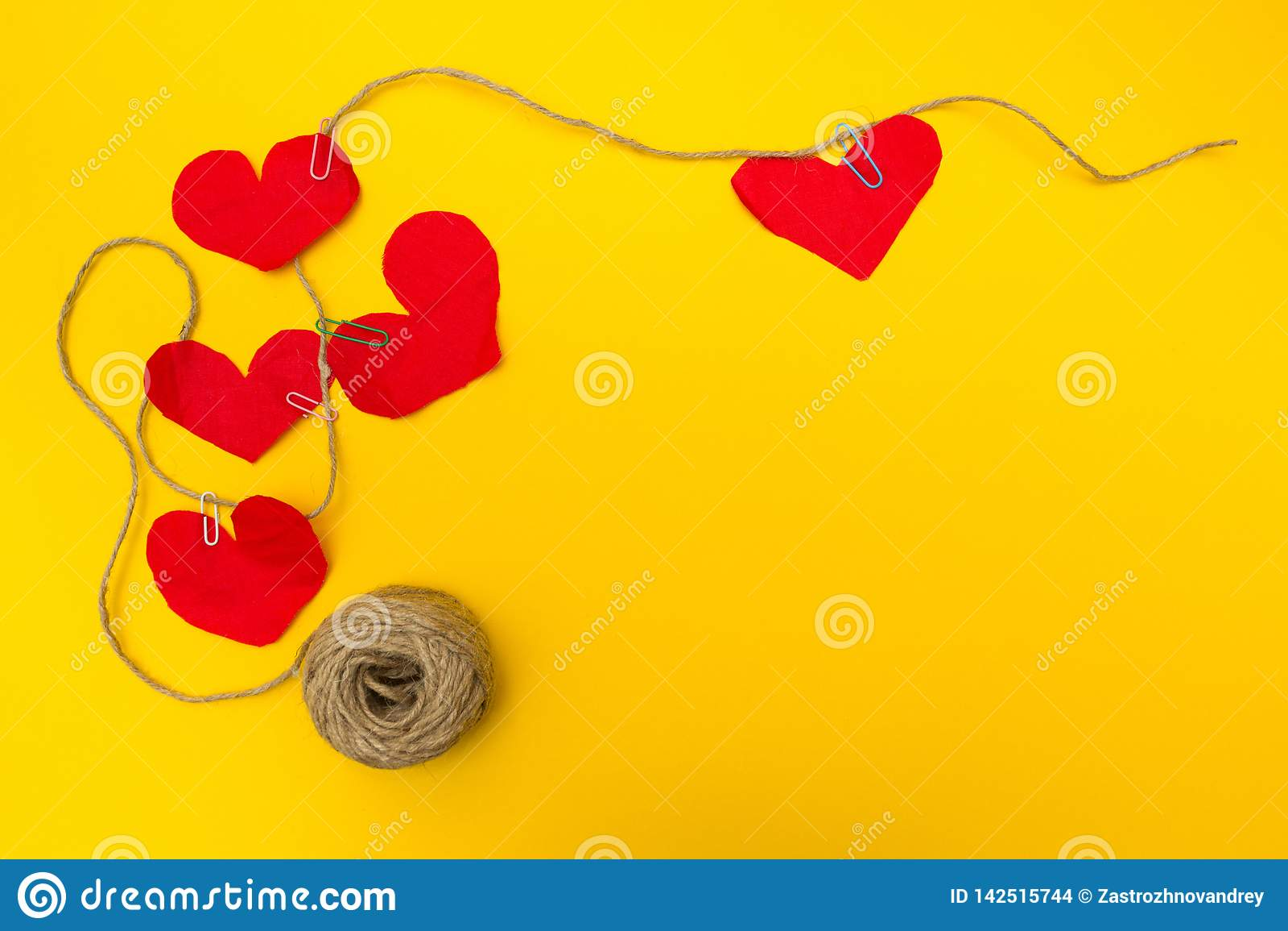 Handgemachtes Seil von fünf roten Herzen, gelber Hintergrund Flache Zusammensetzung
