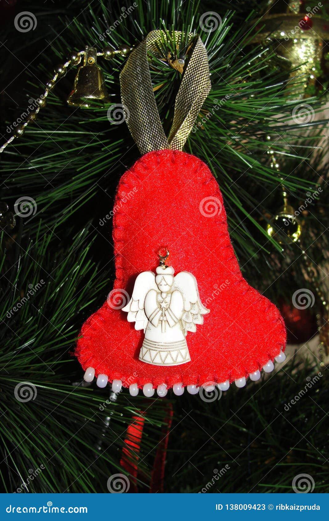 Handgjord julleksak på en julgran Ljus röd klocka som göras av filt
