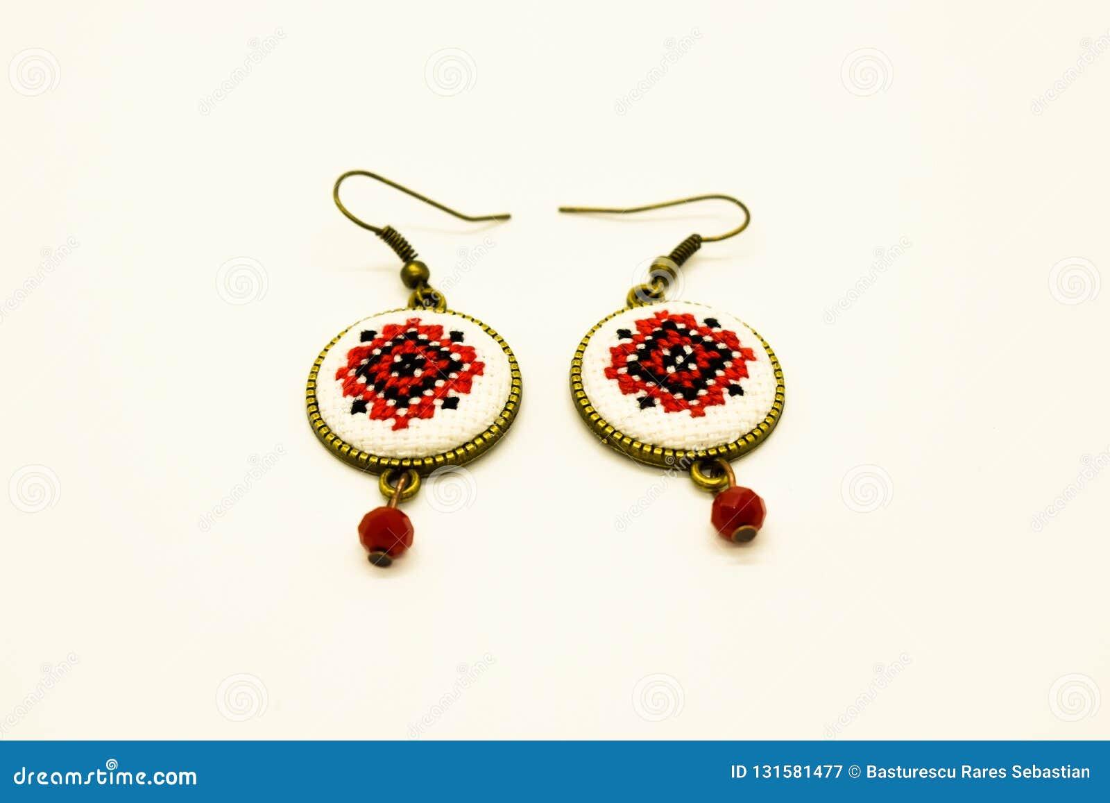 Handgjorda örhängen med den röda och svarta romanian traditionella modellen Isolerat på vit