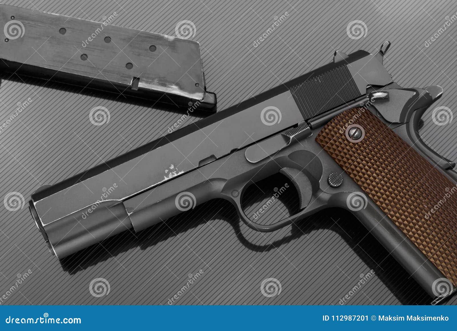 Handgun on dark background with ammo clip
