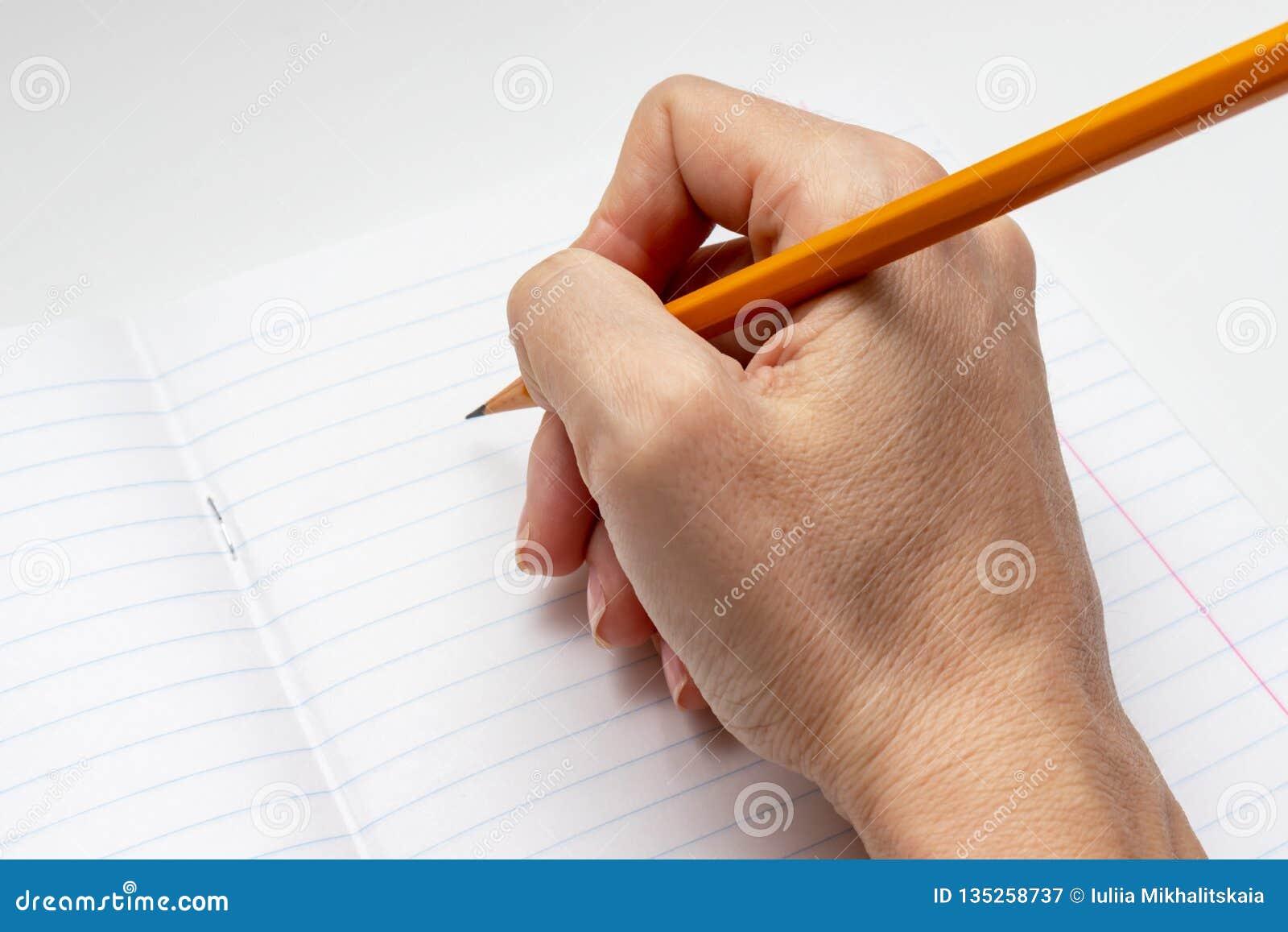 Handhandstil på det vita fodrade arket av anteckningsboken med en gul blyertspenna