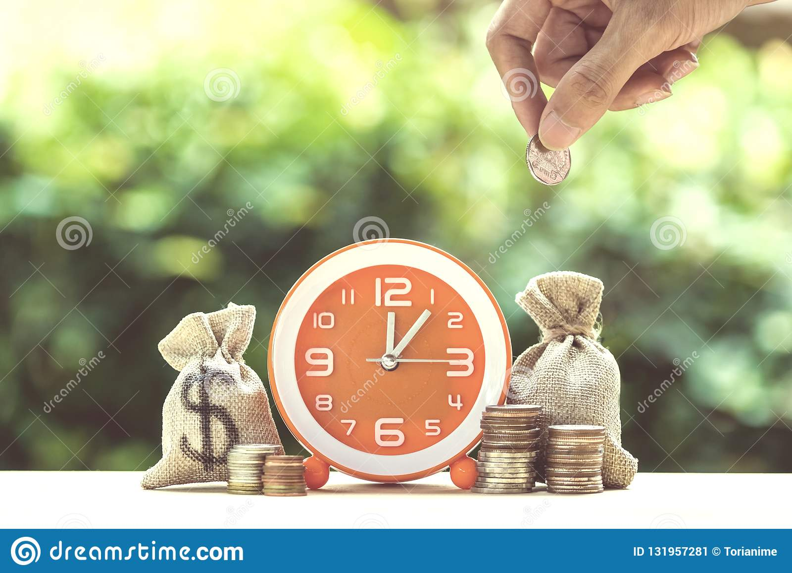 Handholdingmünze über Moneybags und orange Uhr auf hölzernem tabl