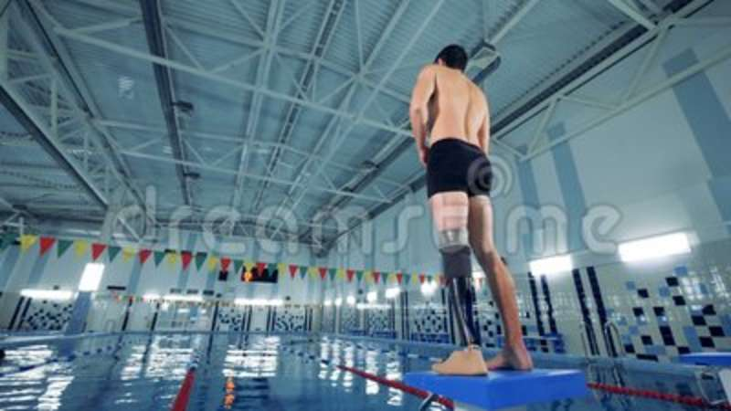 A handicapped swimmer warming up near a pool, back view. Person with prosthesis stands near a pool, warming up stock video footage