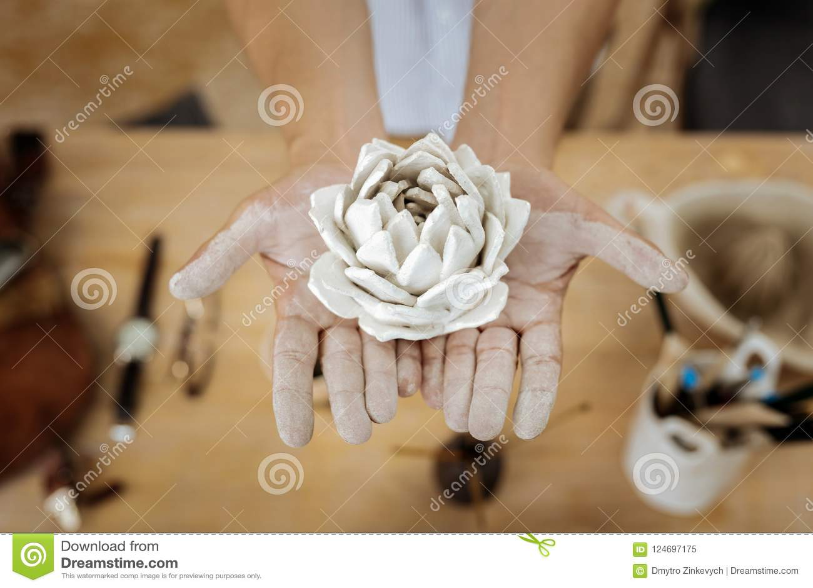Handicraftsman que mostra uma flor surpreendente do produto de cerâmica nas mãos