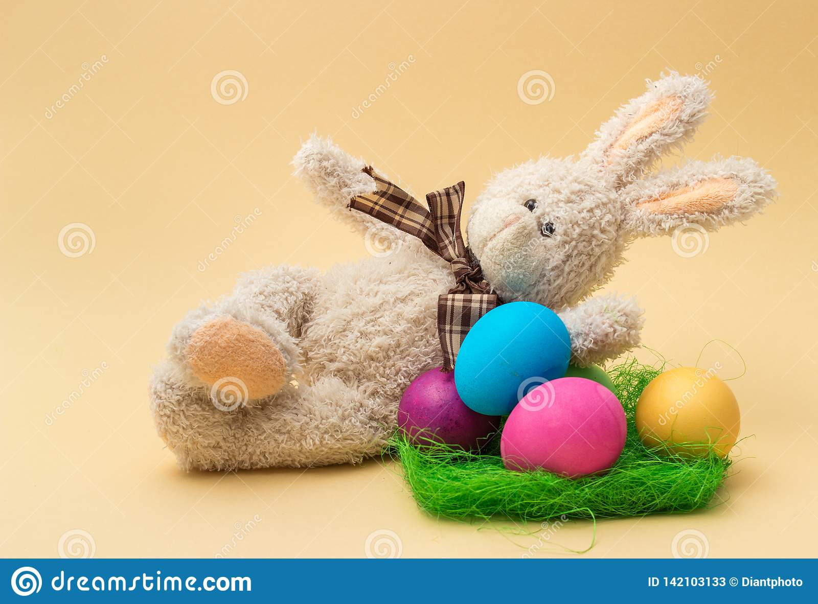 Handmade Bunny and Easter Colored Eggs. Beige background.