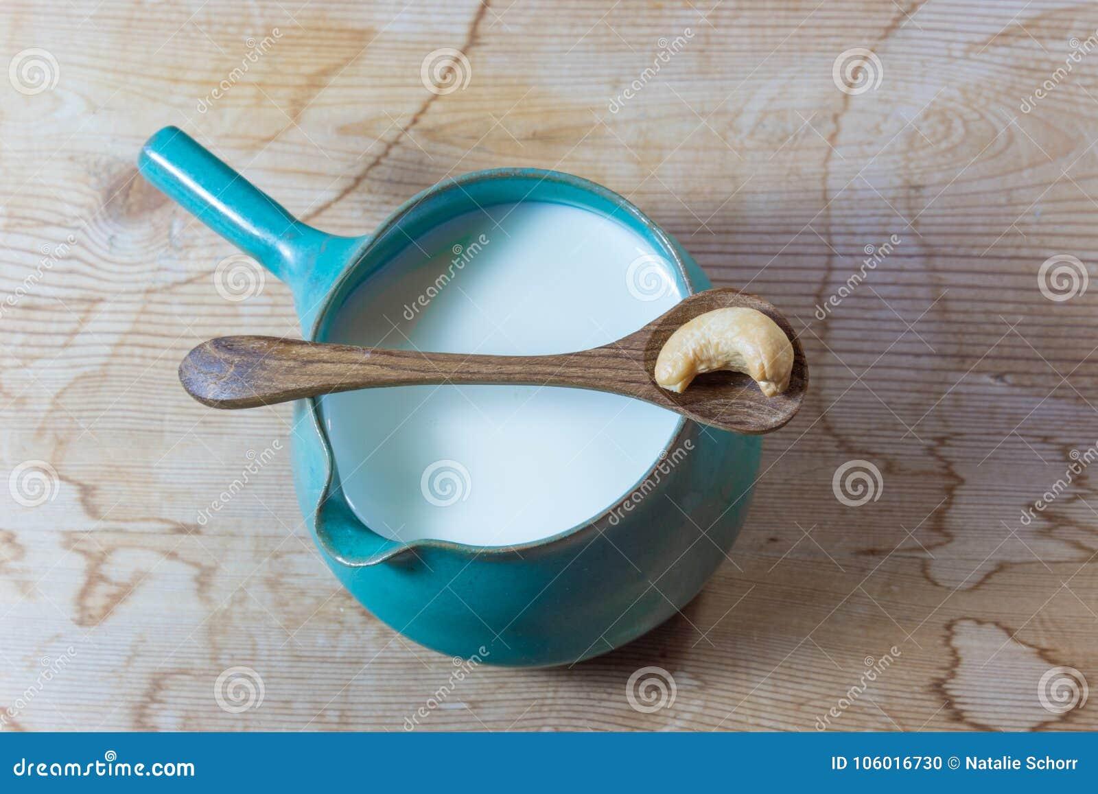 Handmade ceramiczny miotacz nerkodrzewu mleko ześrodkowywał, rocznika drewniany tło, drewniana łyżka z pojedynczym nerkodrzewem