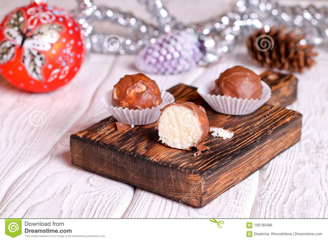 Handmade chocolate coconut candy on wooden table with Christmas