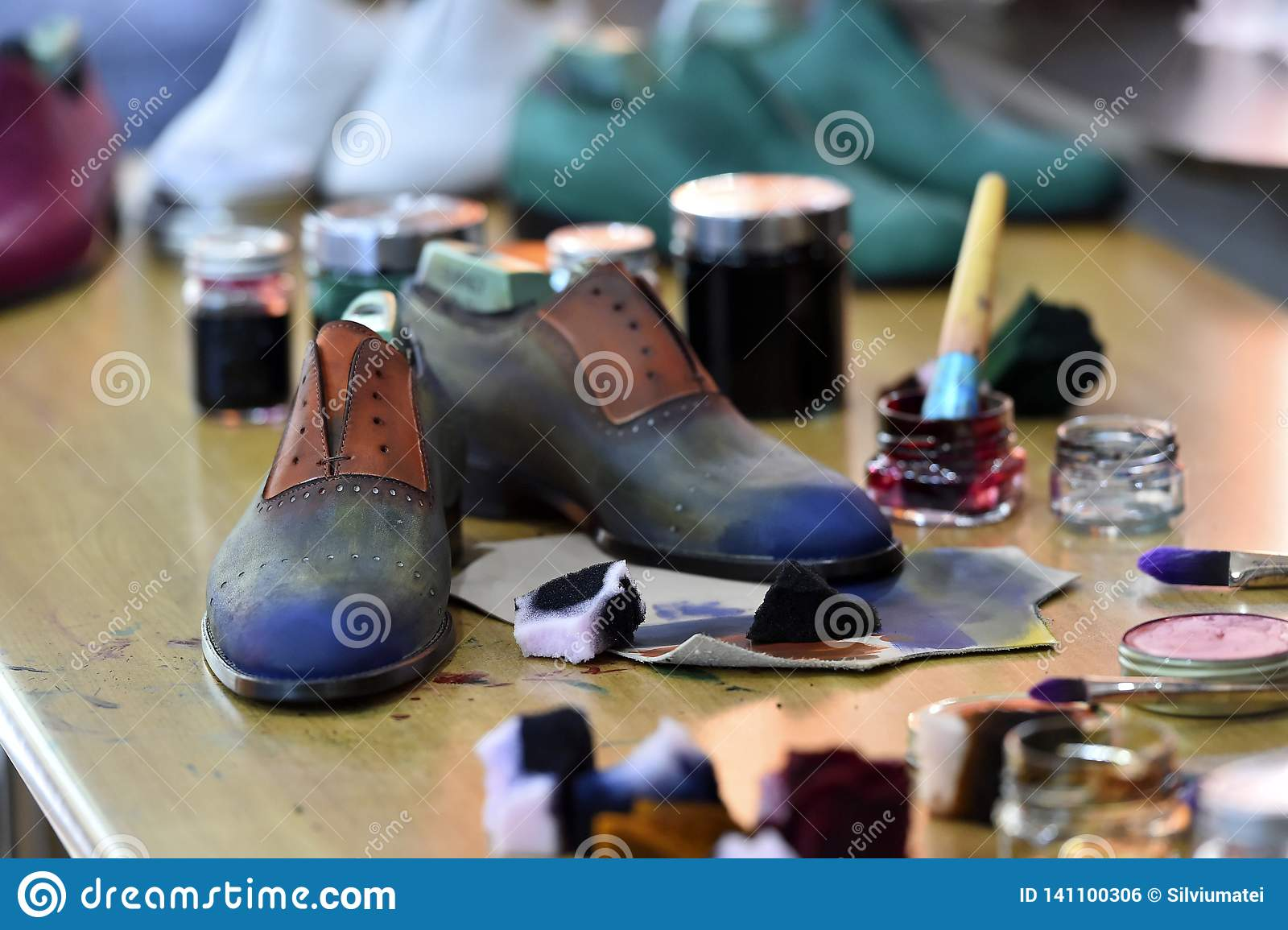 Handmade colorful luxury man shoes are hand-painted in a production factory.