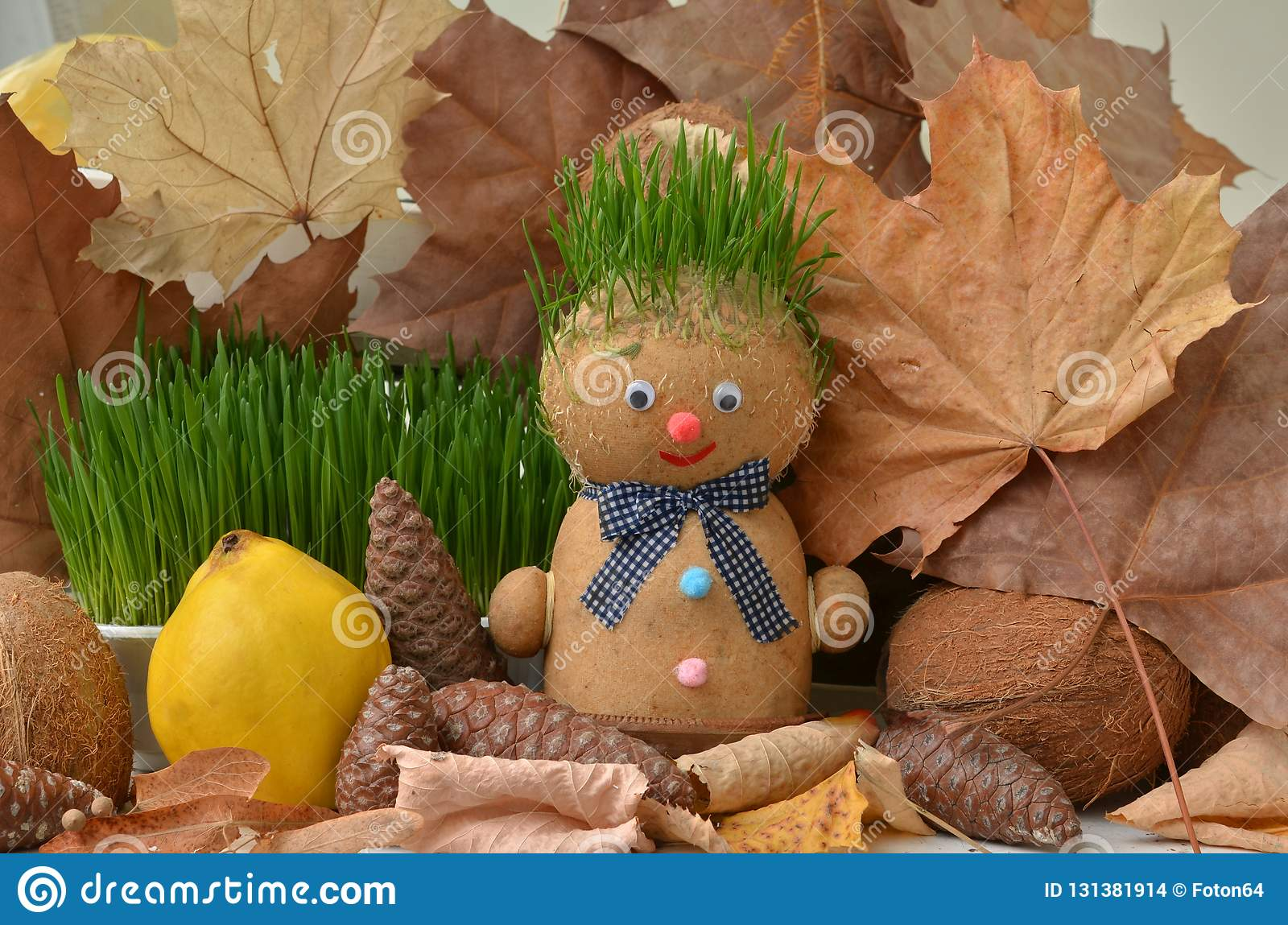 Handmade doll with green grass hair. Autumn still life.