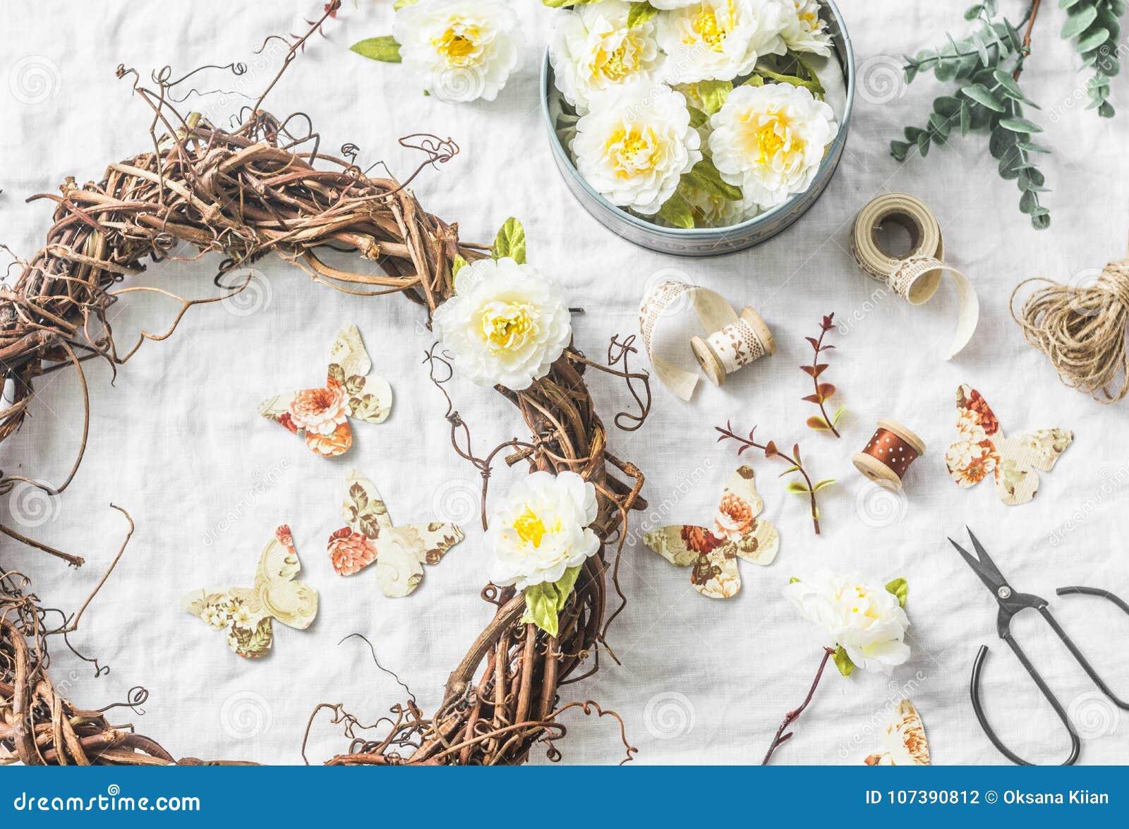 Handmade domowy wewnętrznej dekoraci winorośli wianek z papierowymi kwiatami i motylami na lekkim tle, odgórny widok Mieszkanie n