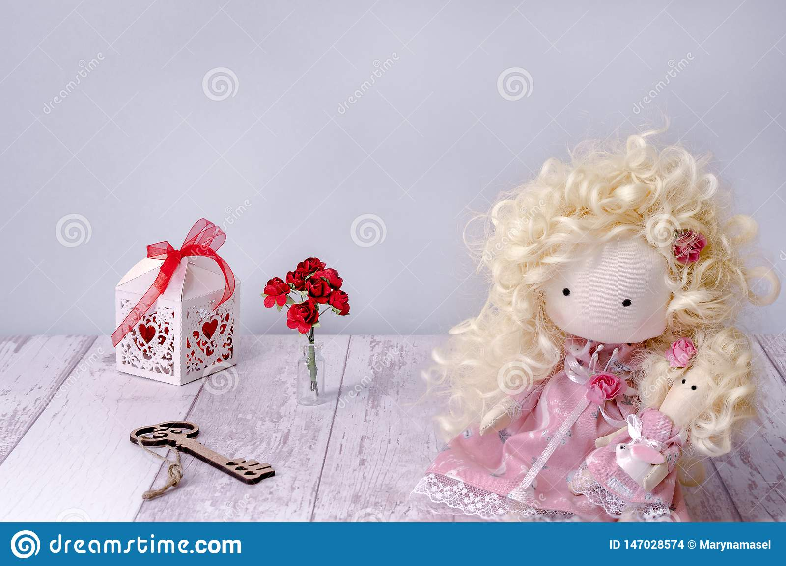 Handmade fabric doll girl on a white wooden table copyspace with fairy key, paper rose and gift box