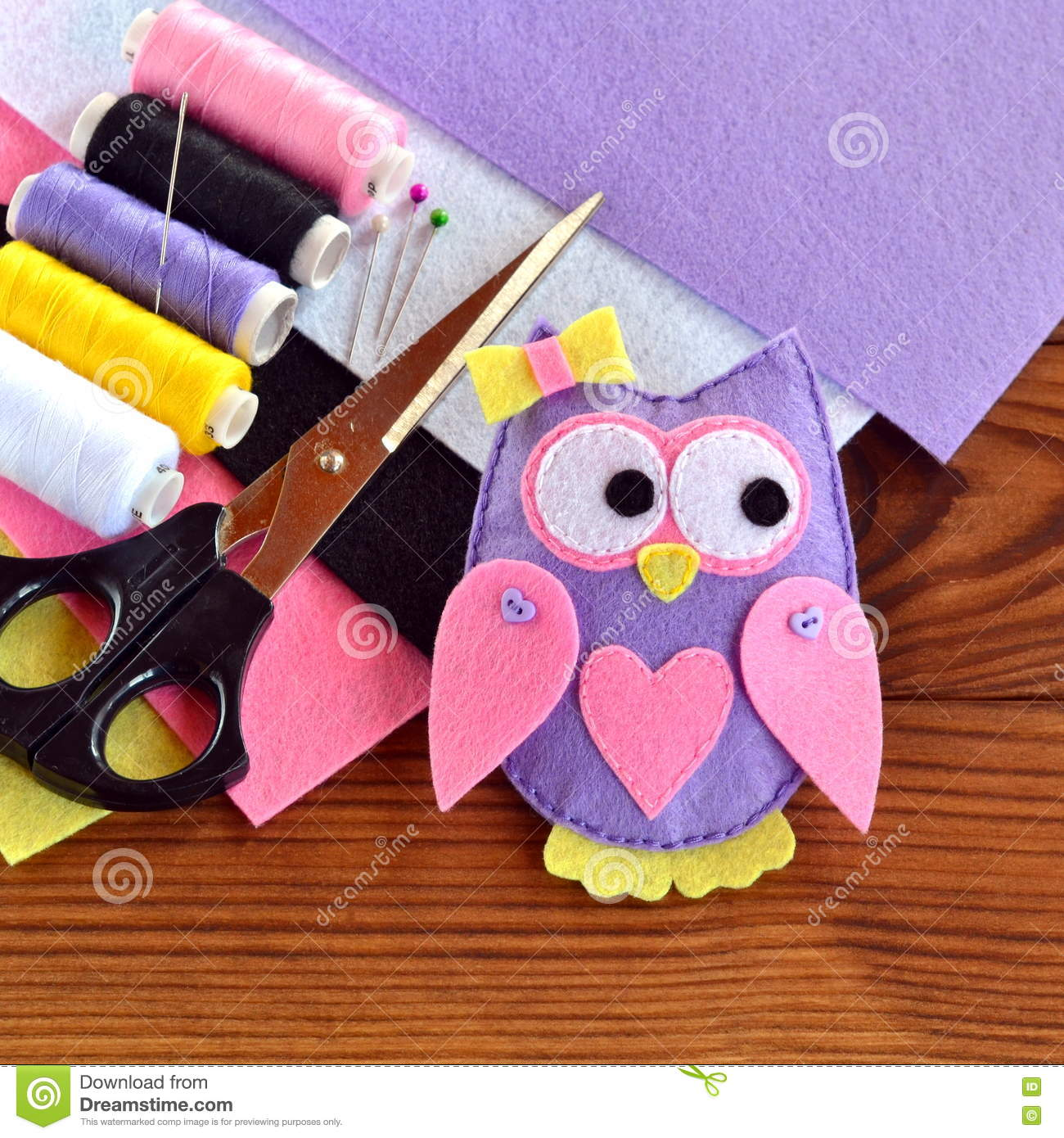 Handmade felt owl toy, felt sheets, scissors, thread, pins, needle on a brown wooden background. Sewing concept