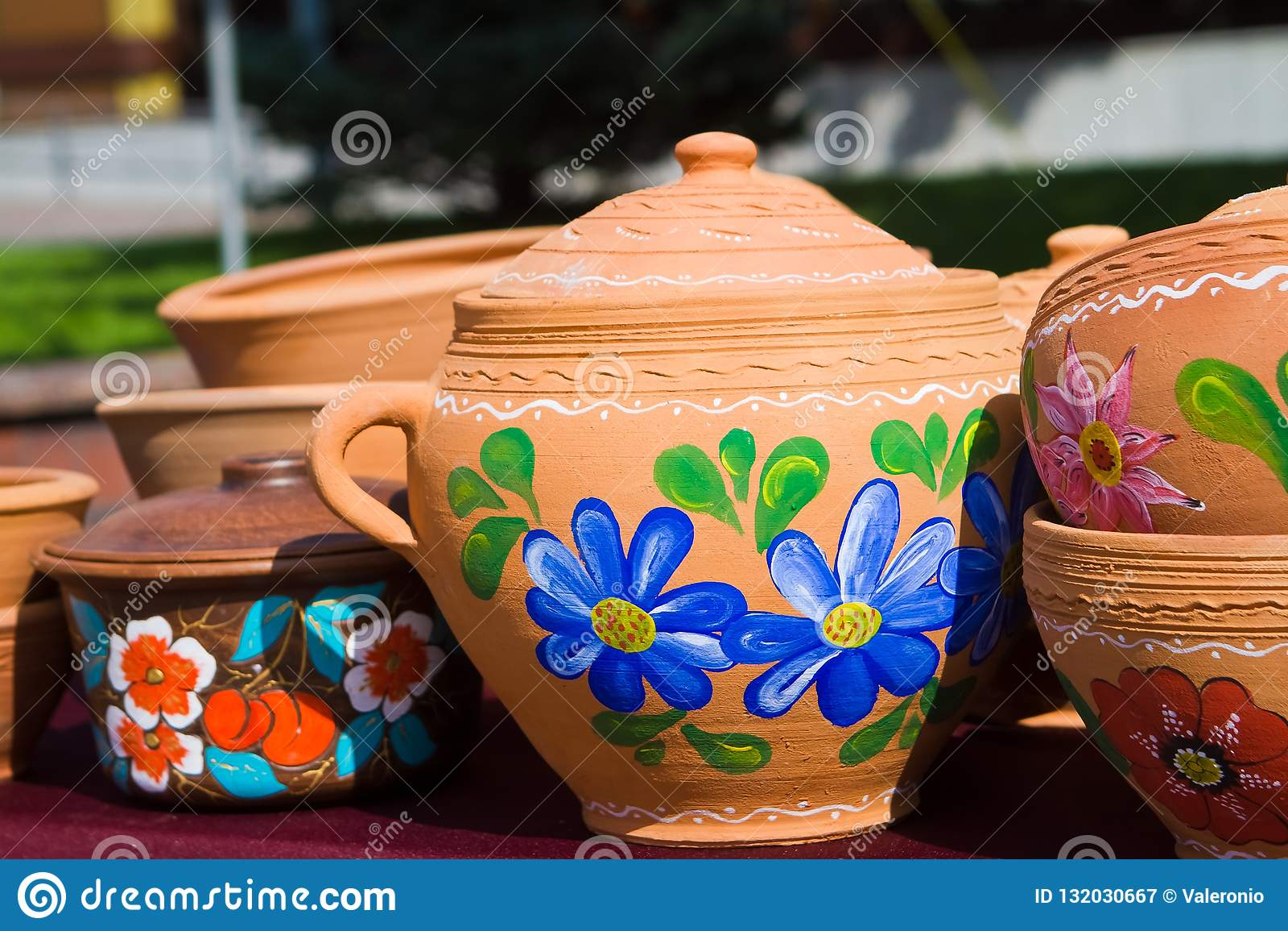 Handmade i handpainted ceramiczni gliniani dzbanki, garnki z pokrywami, jaskrawi kwieciści wzory