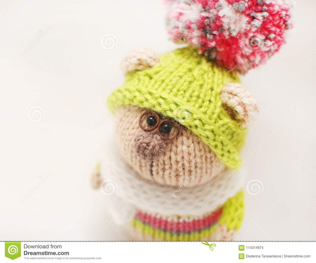 22e24846807 Handmade knitted toy. Knitted bear close-up in color sweater and green cap  with