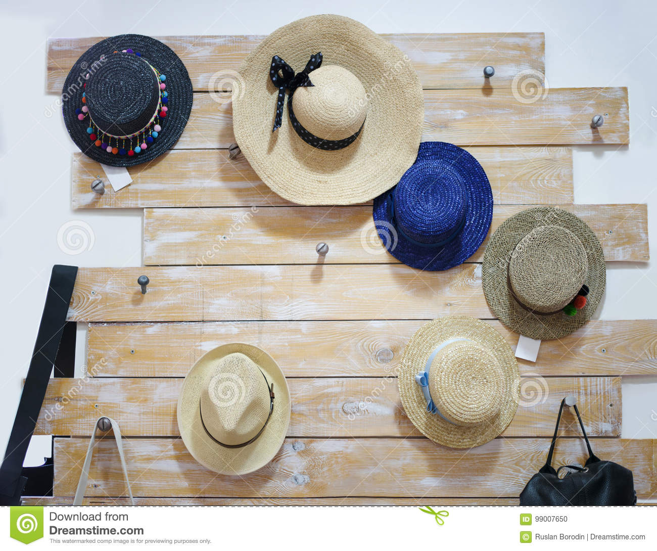 9b3ba9dcf57 Handmade pretty women hats. Classic summer hats hanging in a store on a wall  background. Fancy accessories. Straw hats.