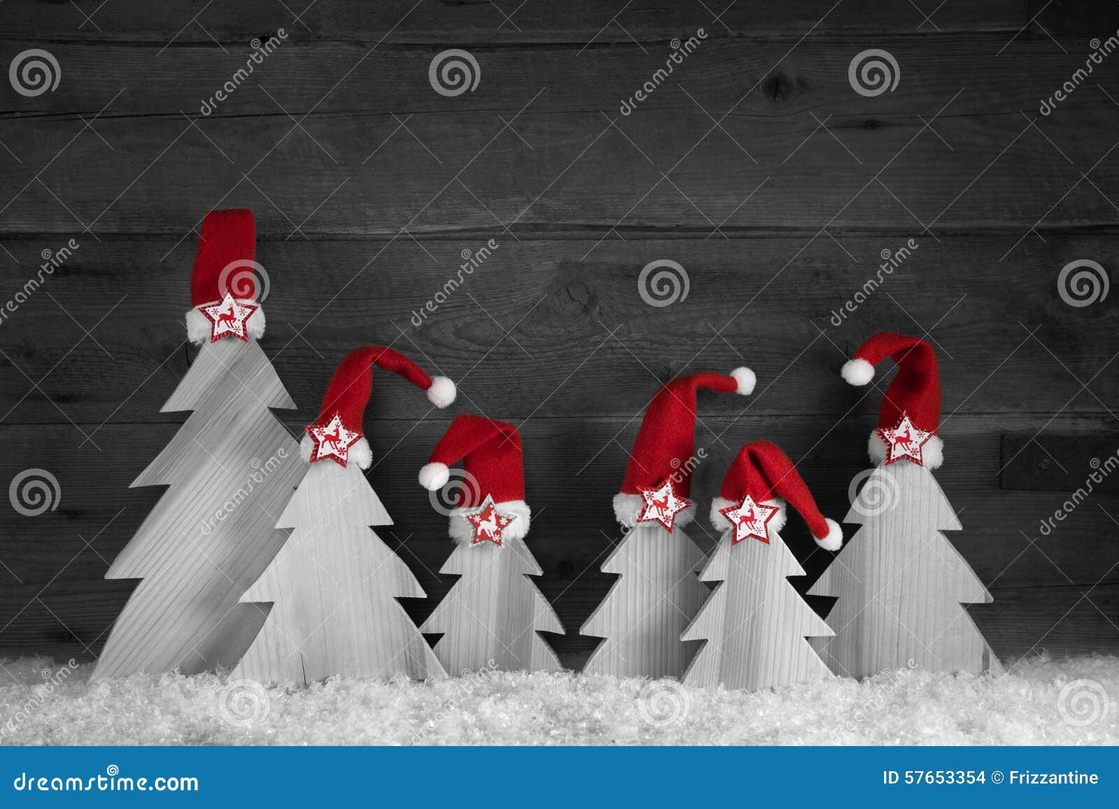 Handmade rzeźbić choinki z czerwonymi Santa kapeluszami na drewnianym ol