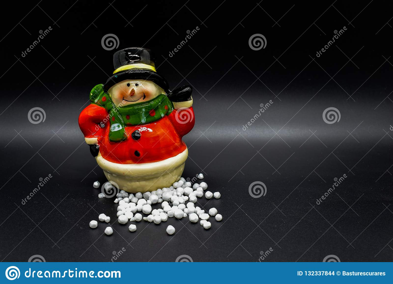 Handmade snowman figurine isolated on black background. Christmas decoration.