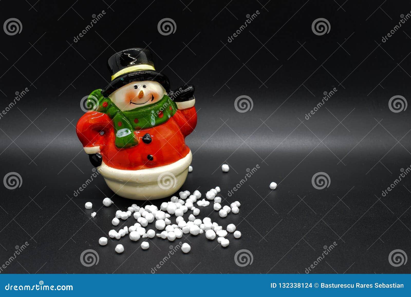 Handmade snowman figurine isolated on black background. Christmas decoration.