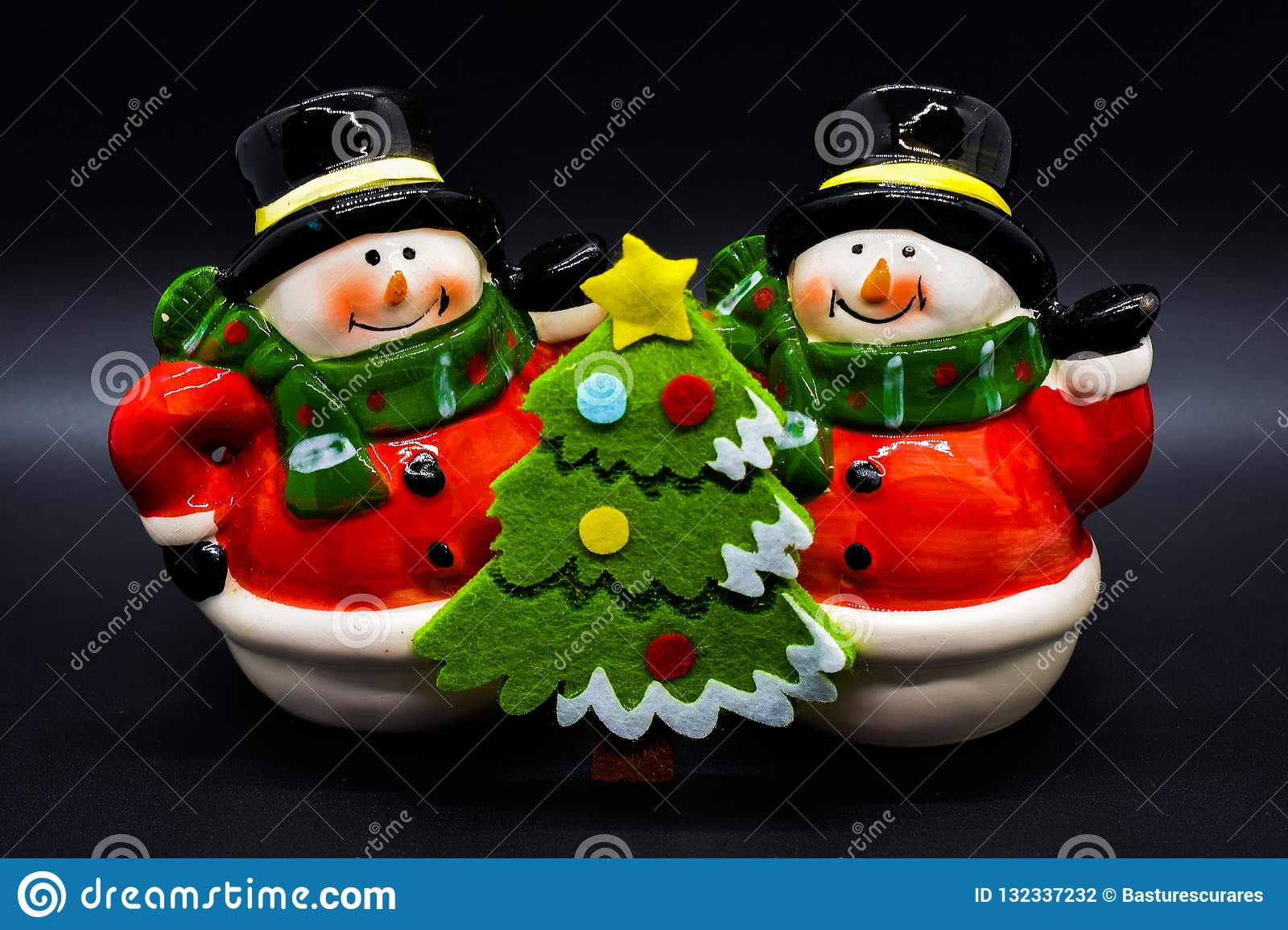 Handmade snowmen figurines isolated on black background. Christmas decoration.