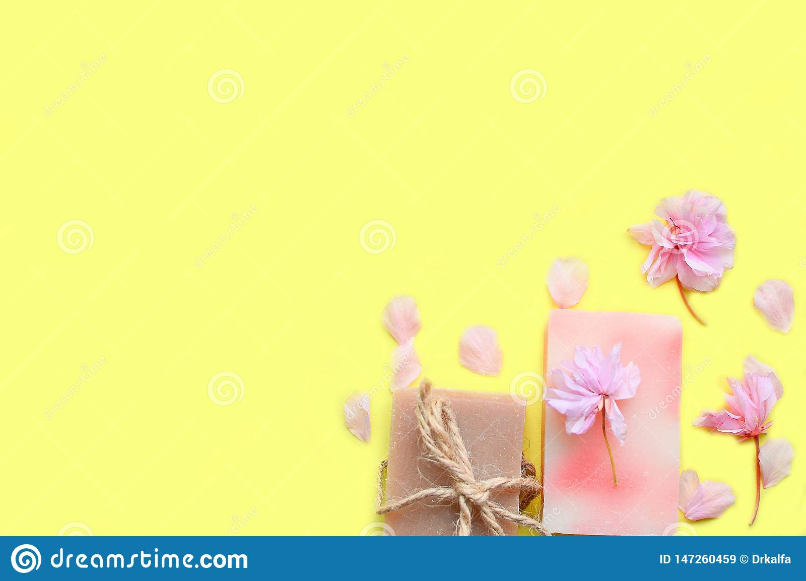 Handmade soap on a yellow background, flower petals.Space for a text