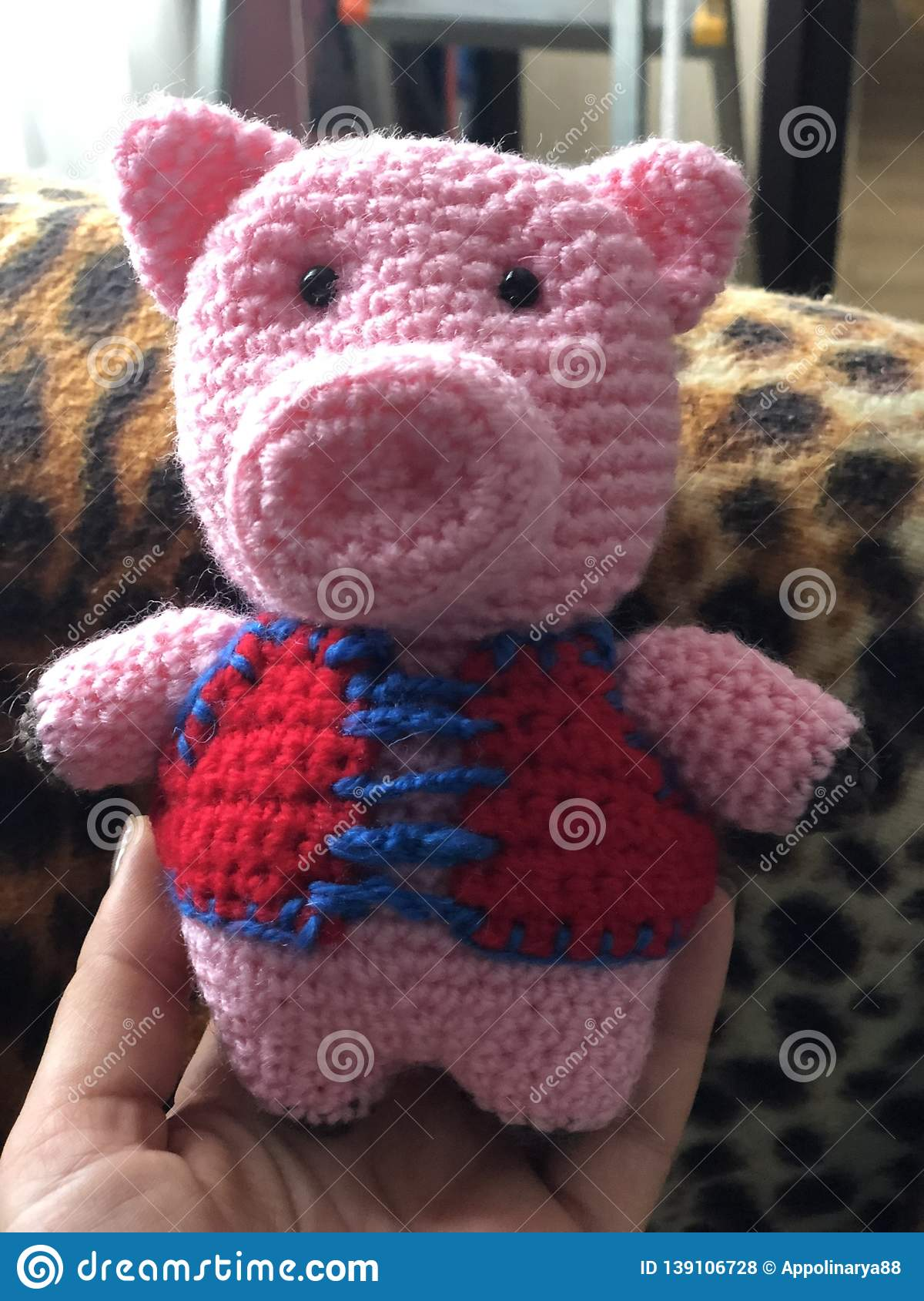 Handmade toy pink knitted pig in red gall