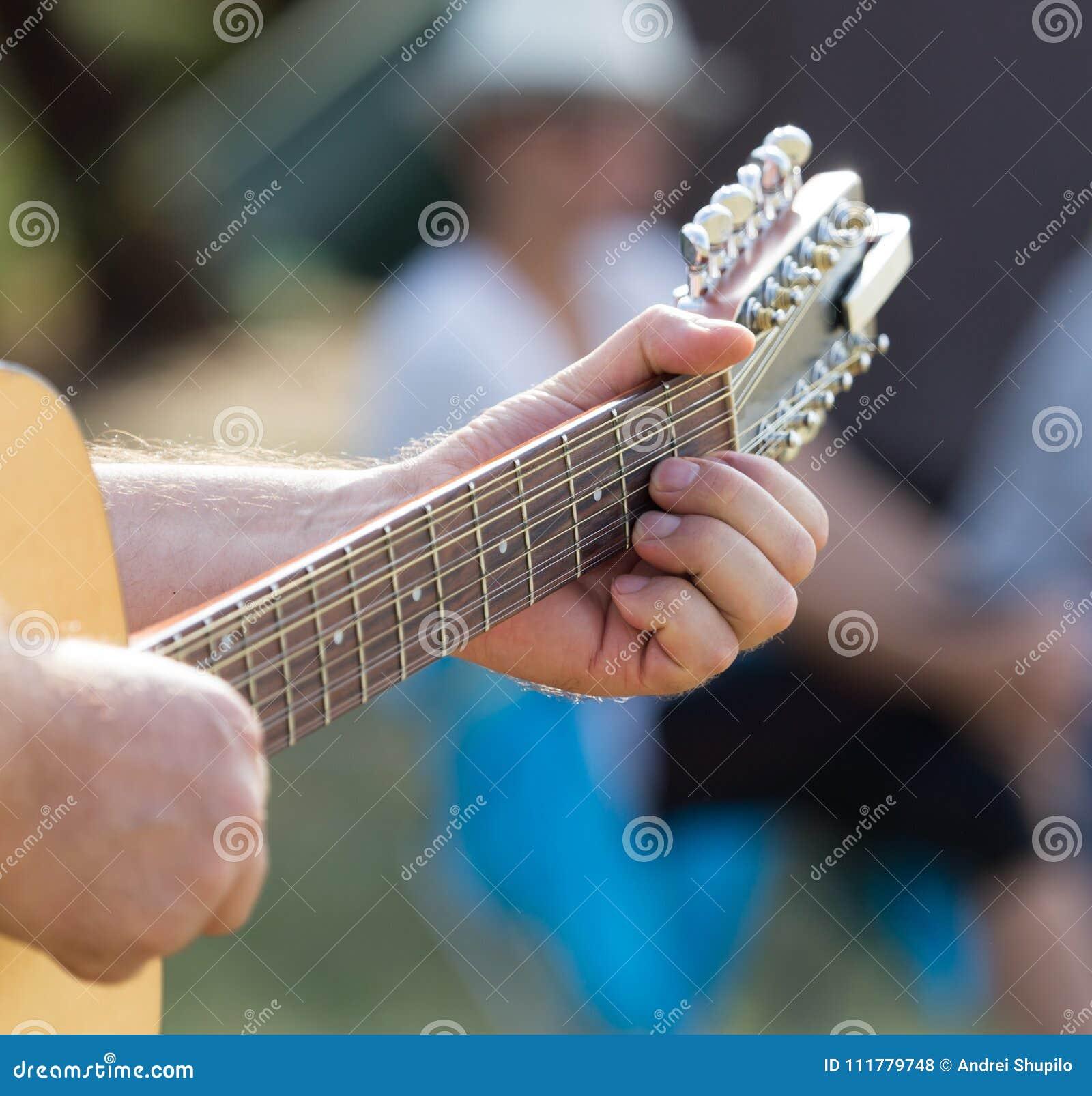 Handman som spelar gitarren