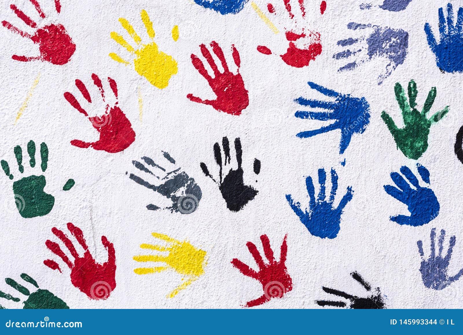 Handprints en amarillo, azul, rojo, verde, se ennegrece en una pared blanca, fondo