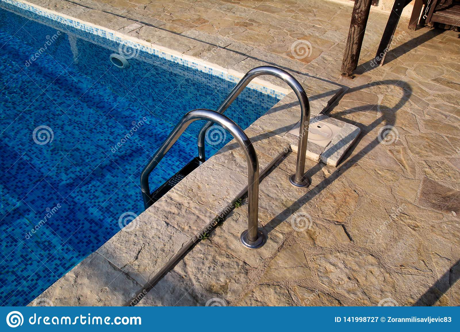 Handrail on pool. Swimming pool with stair at tropical resort. Pool handrails view. Water swimming pool with sunny reflection.
