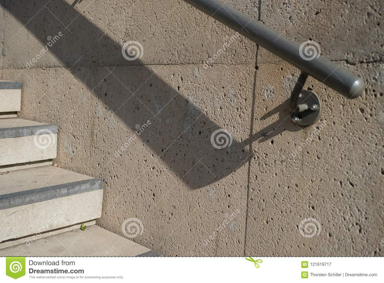 Handrail and stair steps of concrete with deep shadow